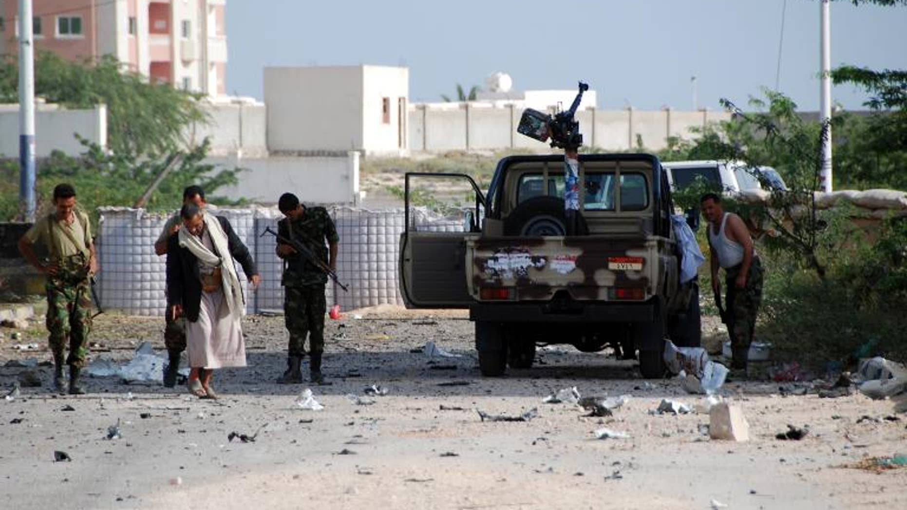 Yemeni security forces are seen along a main road littered with debris after a suicide bomber blew up a vehicle outside a presidential palace in Mukalla on February 25, 2012