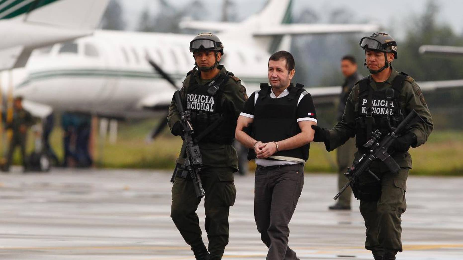 """FILE - In this Tuesday July 9, 2013 file photo, Daniel Barrera, center, is escorted by police to a waiting car prior to his extradition to the U.S. from the counter-narcotics base in Bogota, Colombia. Known as """"El Loco,"""" Spanish for """"The Madman,"""" Barrera is scheduled to be sentenced Mondauy, July 25, 2016, and faces a mandatory minimum of 10 years in prison and up to life after pleading guilty to a drug trafficking charge. (AP Photo/Fernando Vergara, File)"""
