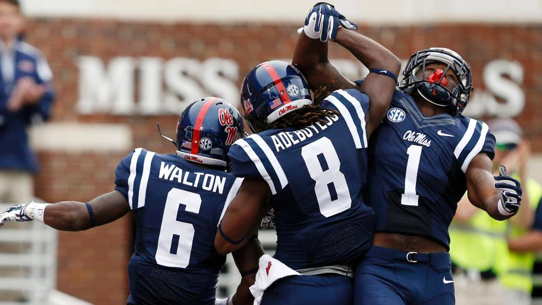 Mississippi running back Jaylen Walton (6) and teammates Quincy Adeboyejo, and Laquon Treadwell (1) celebrate Walton's 71-yard touchdown run against  Louisiana-Lafayette during the second half at an NCAA college football game at Vaught-Hemingway Stadium in Oxford, Miss., Saturday, Sept. 13, 2014. No. 14 Mississippi won 56-15. (AP Photo/Rogelio V. Solis)
