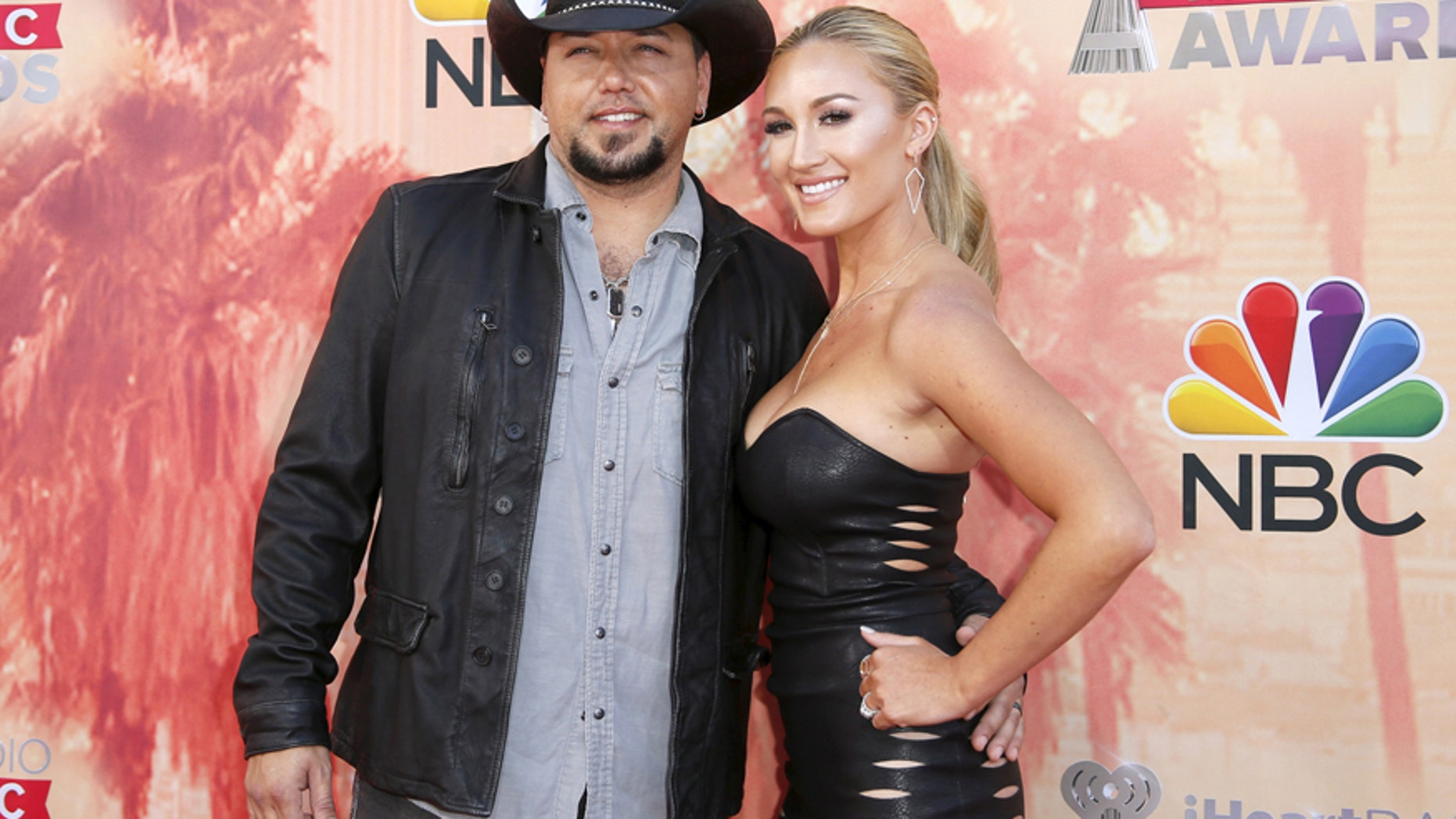 Singer Jason Aldean (L) and wife Brittany Kerr pose at the 2015 iHeartRadio Music Awards in Los Angeles, California, March 29, 2015.