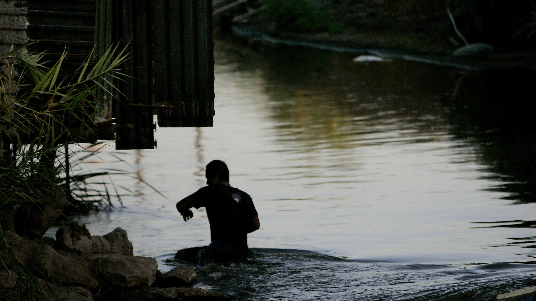 CALEXICO, CA - OCTOBER 9:  A migrant crosses the New River in Calexico, California October 9, 2007.  Immigration continues to be a hot topic among political contenders and economic watchdogs.  (Photo by Sandy Huffaker/Getty Images)