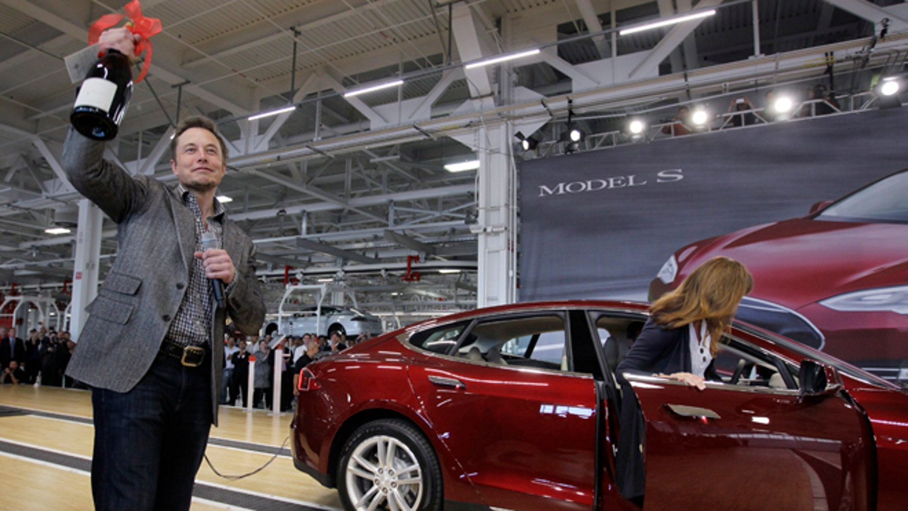 FILE - In this June 22, 2012 file photo, Tesla Motors Inc. CEO Elon Musk holds up a bottle of wine given as a gift from one of their first customers, right, during a rally at the Tesla factory in Fremont, Calif. Tesla Motors says it is preparing a site near Reno, Nevada, as a possible location for its new battery factory, but is still evaluating other locations. (AP Photo/Paul Sakuma, File)