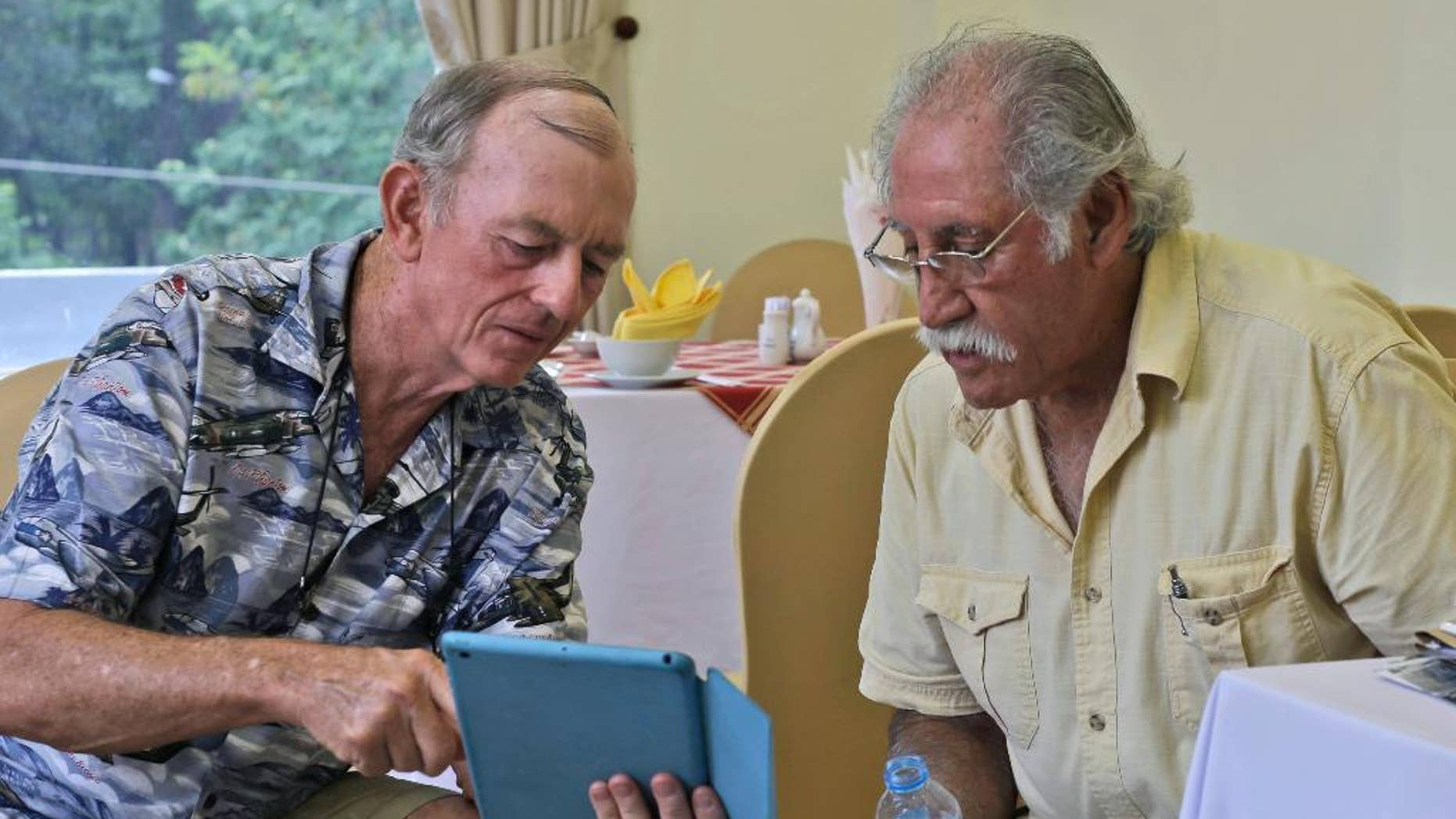 In this Tuesday, April 28, 2015 photo, former U.S. Marines Sgt. Kevin Maloney, left, of Hollywood, Florida, and Master Gunnery Sgt. Juan Valdez, of Oceanside, Calif., browse some photos on Maloney's tablet in Ho Chi Minh City, Vietnam. On the 40th anniversary of the fall of Saigon, 13 Marines who were there that day returned to dedicate a plague to their two fallen comrades at the site of the old embassy, which is now the U.S. Consulate. (AP Photo/Dita Alangkara)