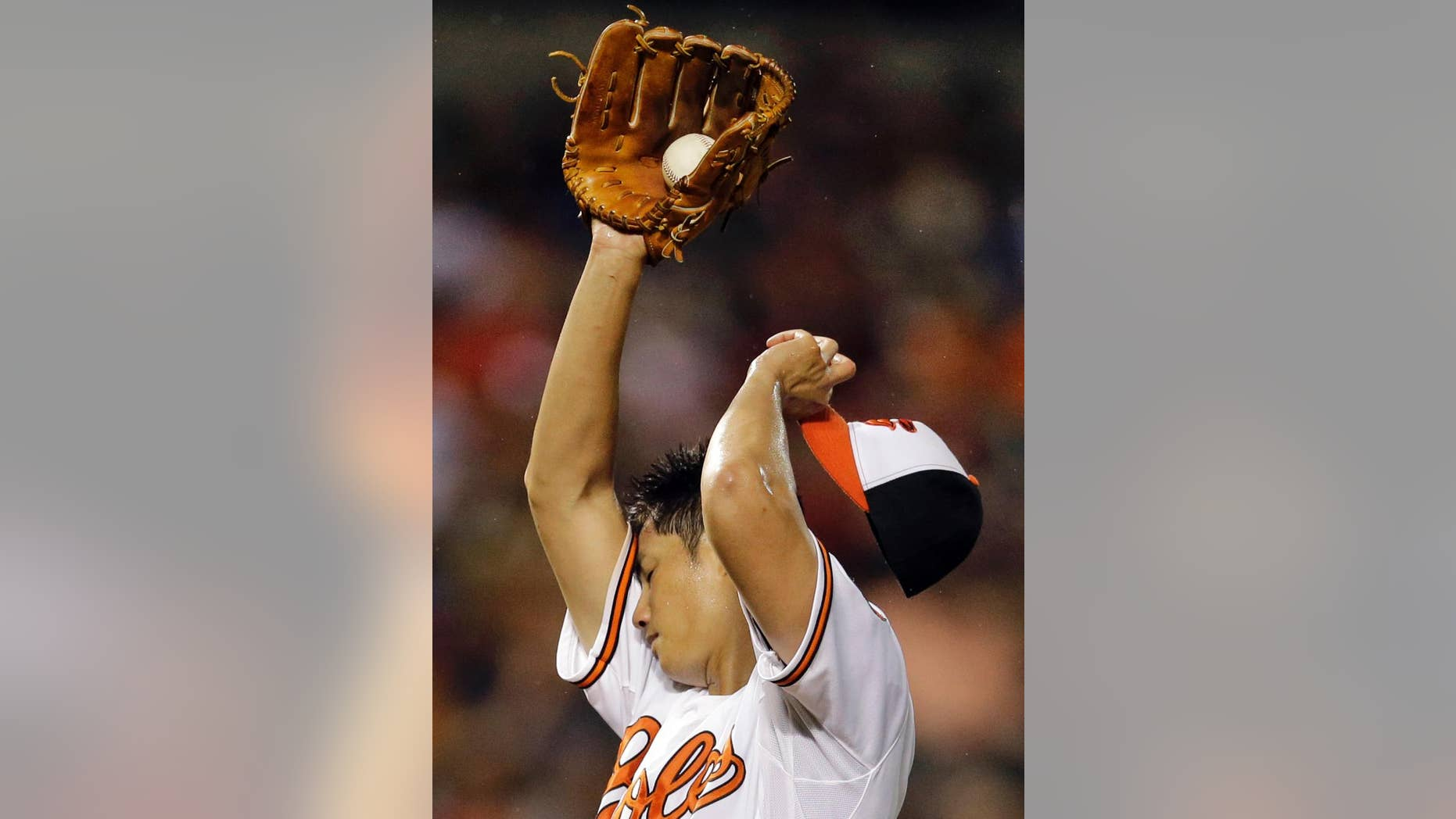 Baltimore Orioles starting pitcher Wei-Yin Chen, of Taiwan,  wipes sweat from his face after Washington Nationals'  Ryan Zimmerman doubled in the sixth inning of an interleague baseball game, Thursday, July 10, 2014, in Baltimore. Chen was relieved later in the sixth. (AP Photo/Patrick Semansky)