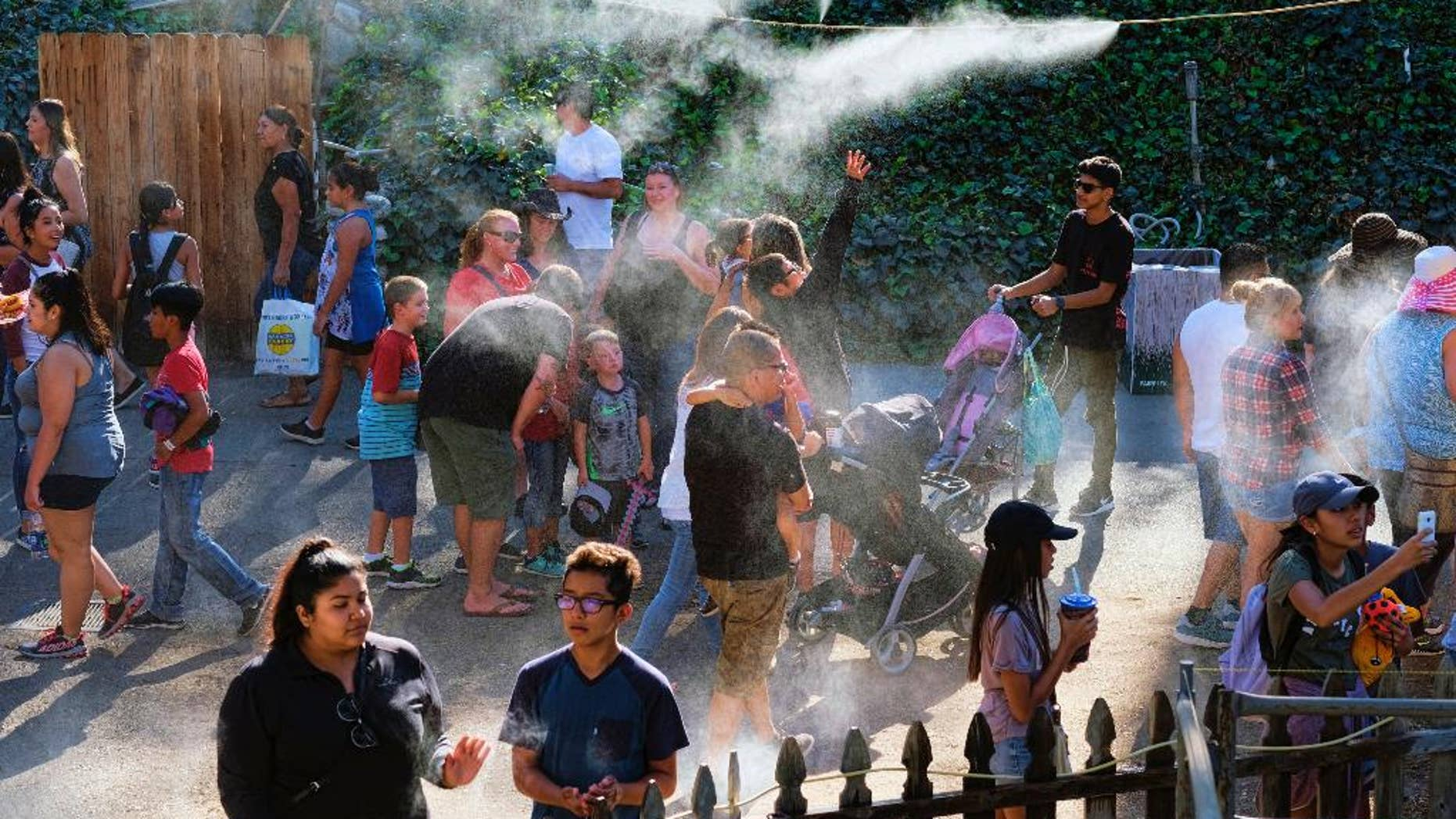 In this Saturday, Sept. 24, 2016 photo, visitors to the Los Angeles County fair cool off under outdoor misters in Pomona, Calif. Californians braced Monday, Sept. 26 for another hot autumn day as forecasters warned of soaring temperatures and potential wildfires due to hot, dry and windy conditions. (AP Photo/Richard Vogel)