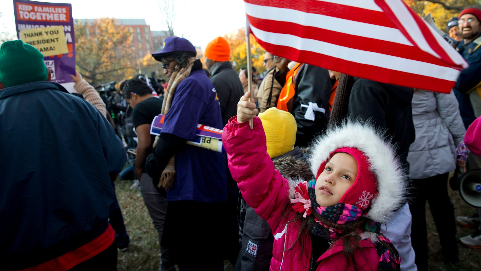 Joselyn Vargas, 7, of Hyattsville, Md., waves a U.S. flag during a rally in Lafayette Park across from the White House in Washington, Friday, Nov. 21, 2014, thanking President Obama for his executive action on illegal immigratio. Vargas' parents are eligible under the executive action as the girl and her younger sister are U.S. citizens. (AP Photo/Jacquelyn Martin)