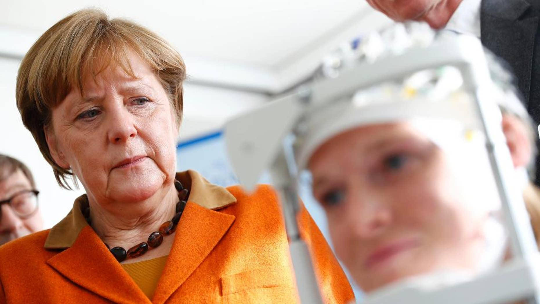 German Chancellor Angela Merkel visits the section for measuring brain waves at the new research center for dementia diseases DZNE at the university hospital in Bonn, Germany, Wednesday, March 15, 2017. (Wolfgang Rattay/Pool Photo via AP
