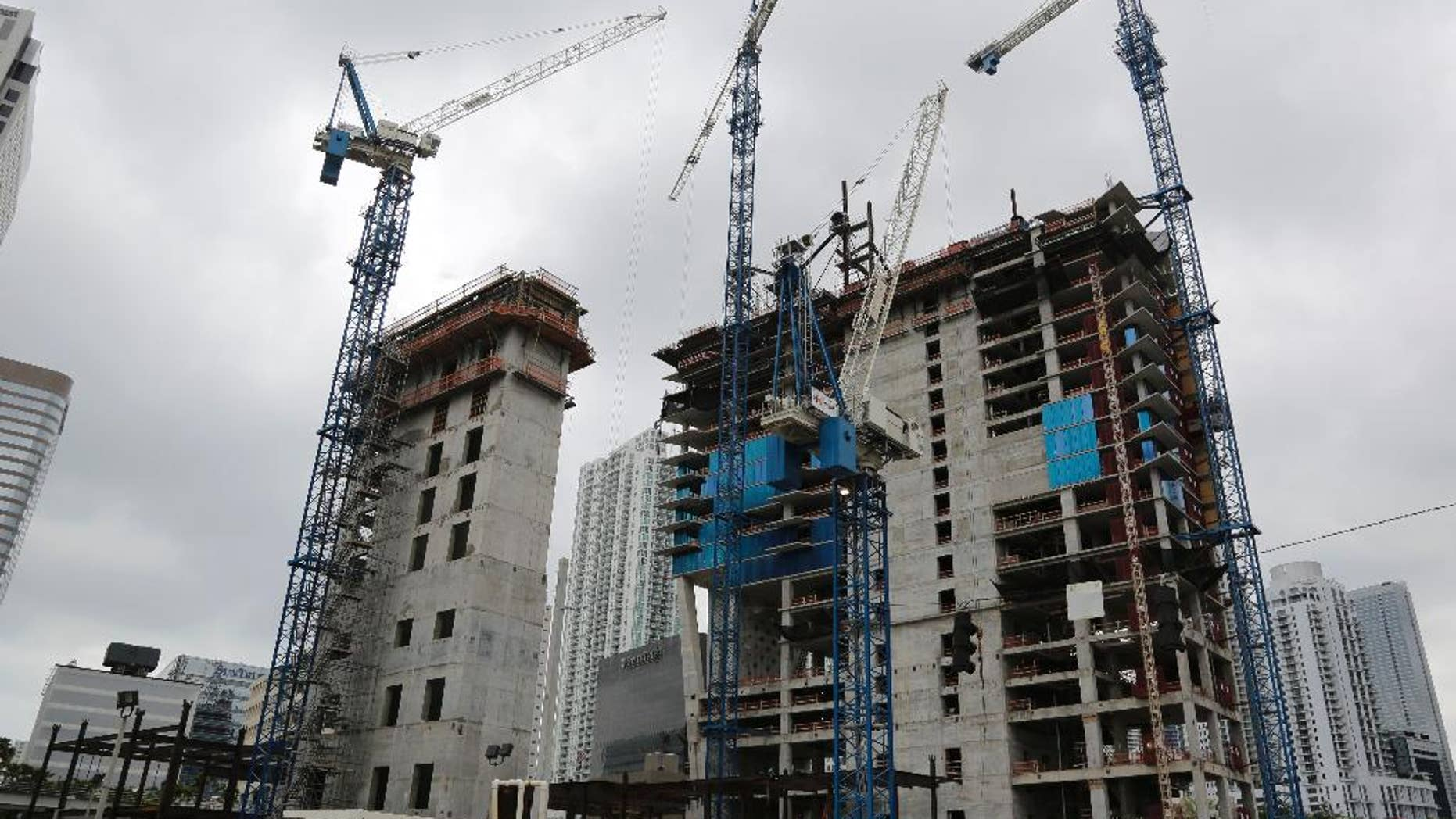 In this Friday, May 16, 2014 photo, cranes fill the skyline at the Brickell CityCentre construction site located in the center of the Brickell financial district in downtown Miami. The project is mixed use office, residential, hotel, retail and entertainment space. The Commerce Department reports on U.S. construction spending in May on Tuesday, July 1, 2014. (AP Photo/Lynne Sladky)