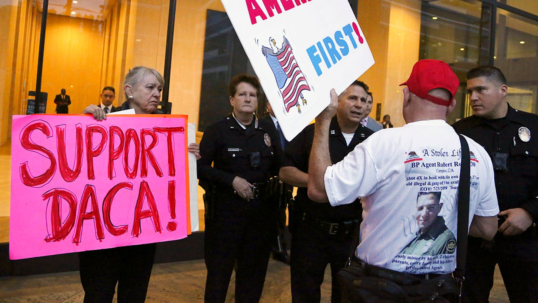 A supporter of President Donald Trump challenges police officers and a Deferred Action for Childhood Arrivals (DACA) program during a rally outside the office of California Democratic Sen. Dianne Feinstein in Los Angeles, Wednesday, Jan. 3, 2018. (AP Photo/Reed Saxon)