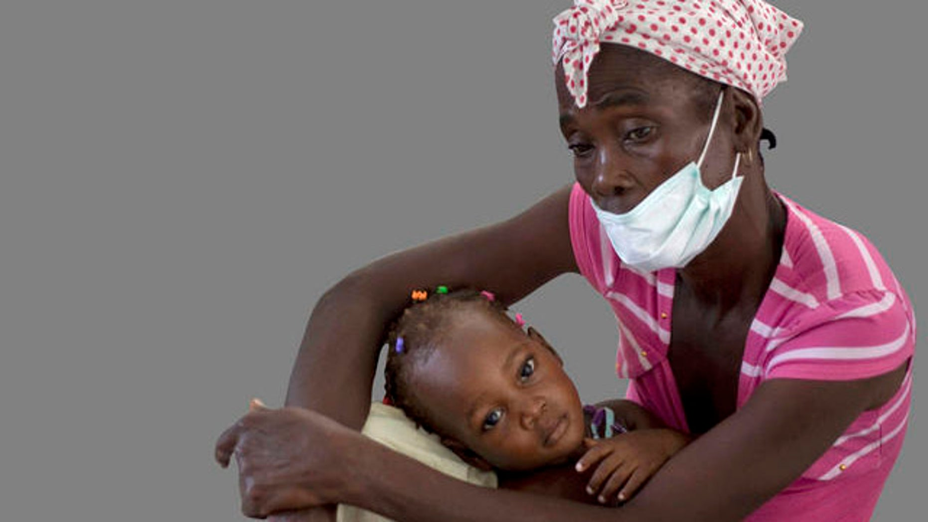 A woman holds her young daughter wile receiving medical attention at St. Nicholas hospital in Saint Marc, Haiti, Friday, Oct. 22, 2010. An outbreak of cholera in rural central Haiti has killed at least 142 people and sickened hundreds more who overwhelmed the hospital in Saint Marc seeking treatment. (AP Photo/Ramon Espinosa)
