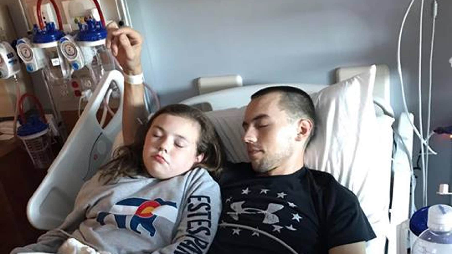 Grace rests next to her father, Jeff, as he recovers in the hospital.