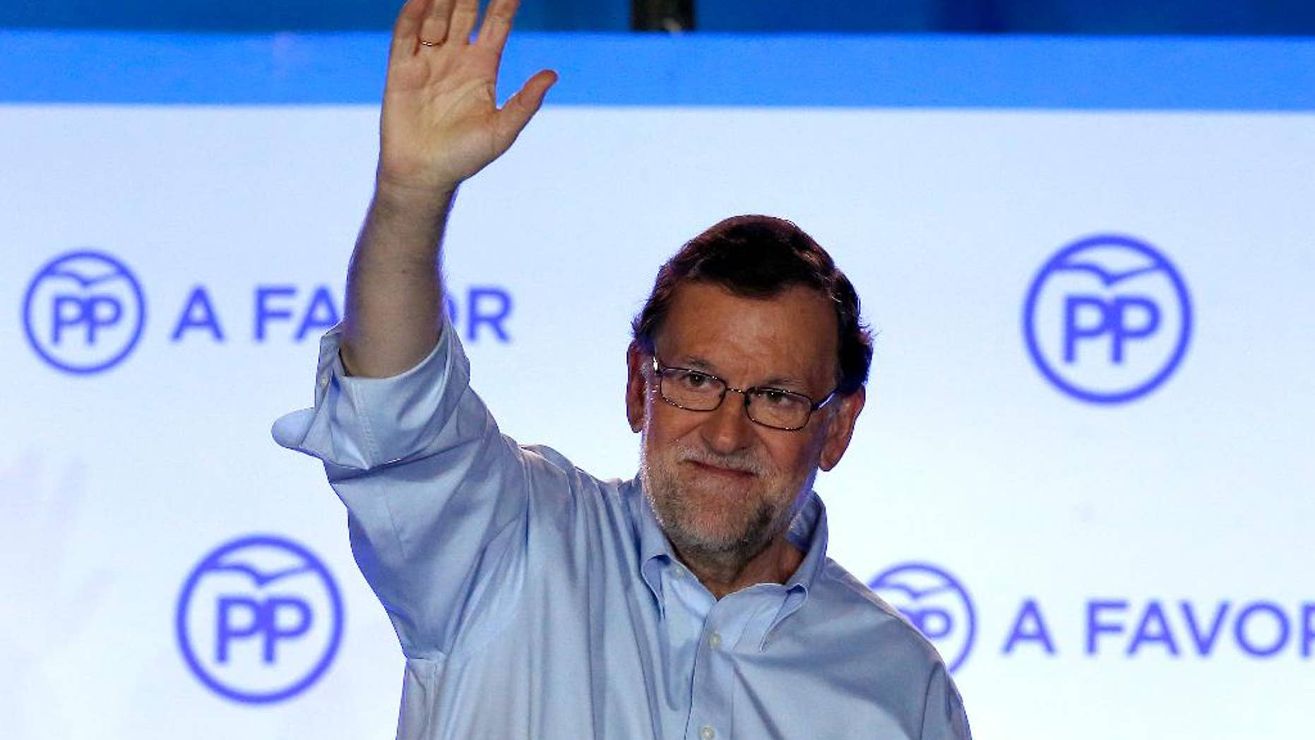 FILE - In this Sunday, June 26, 2016 file photo, Spain's then acting Primer Minister and candidate of Popular Party Mariano Rajoy, waves to his supporters as he celebrates the results of the party during the national elections in Madrid, Spain. Rajoy was re-elected as the leader of the conservative Popular Party for a fourth term on Saturday, Feb. 11, 2017. The 61-year-old Rajoy ran unopposed and won with 95% of the vote at the party congress in Madrid. (AP Photo/Daniel Ochoa de Olza, File)