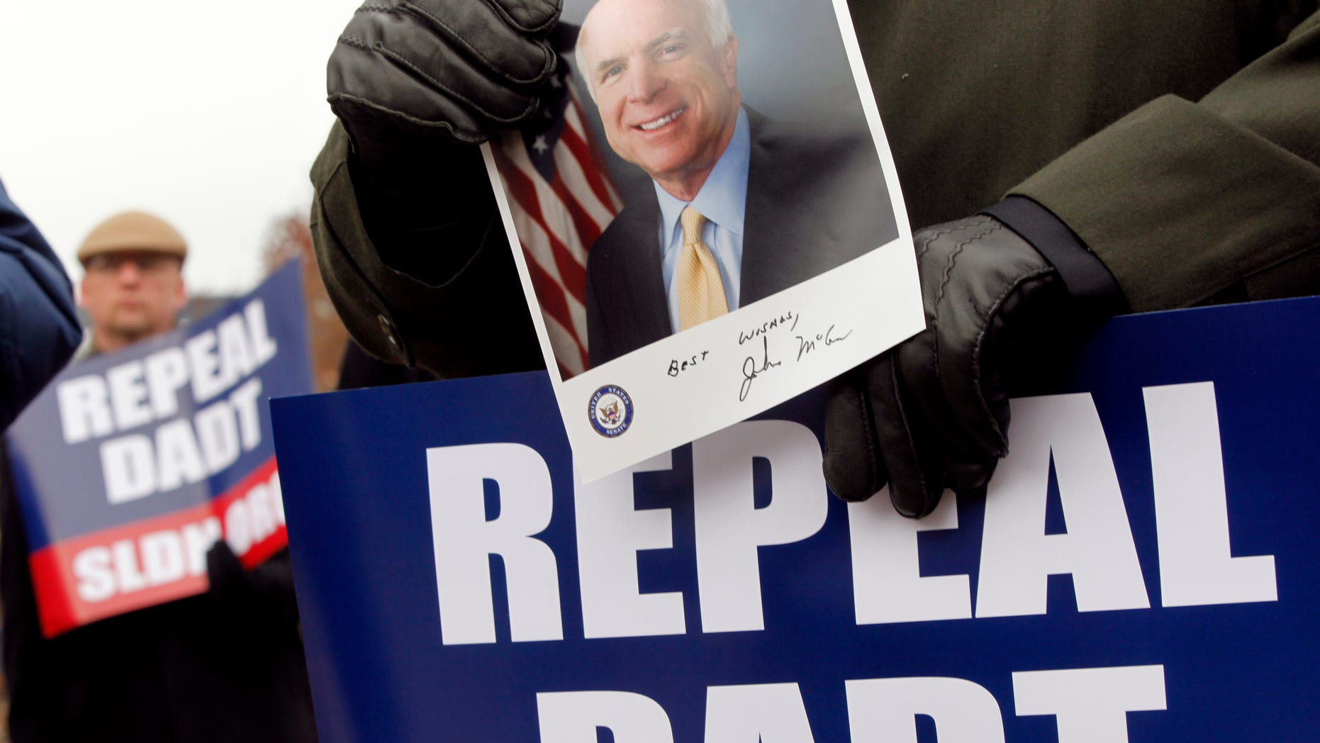 """A supporter of a bill to overturn the military's """"don't ask, don't tell"""" policy holds up a portrait of Sen. John McCain, R-Ariz., who opposes the amendment to repeal the military's 17-year-old ban on openly gay troops, Friday, Dec. 10, 2010, during a rally on Capitol Hill in Washington. (AP)"""