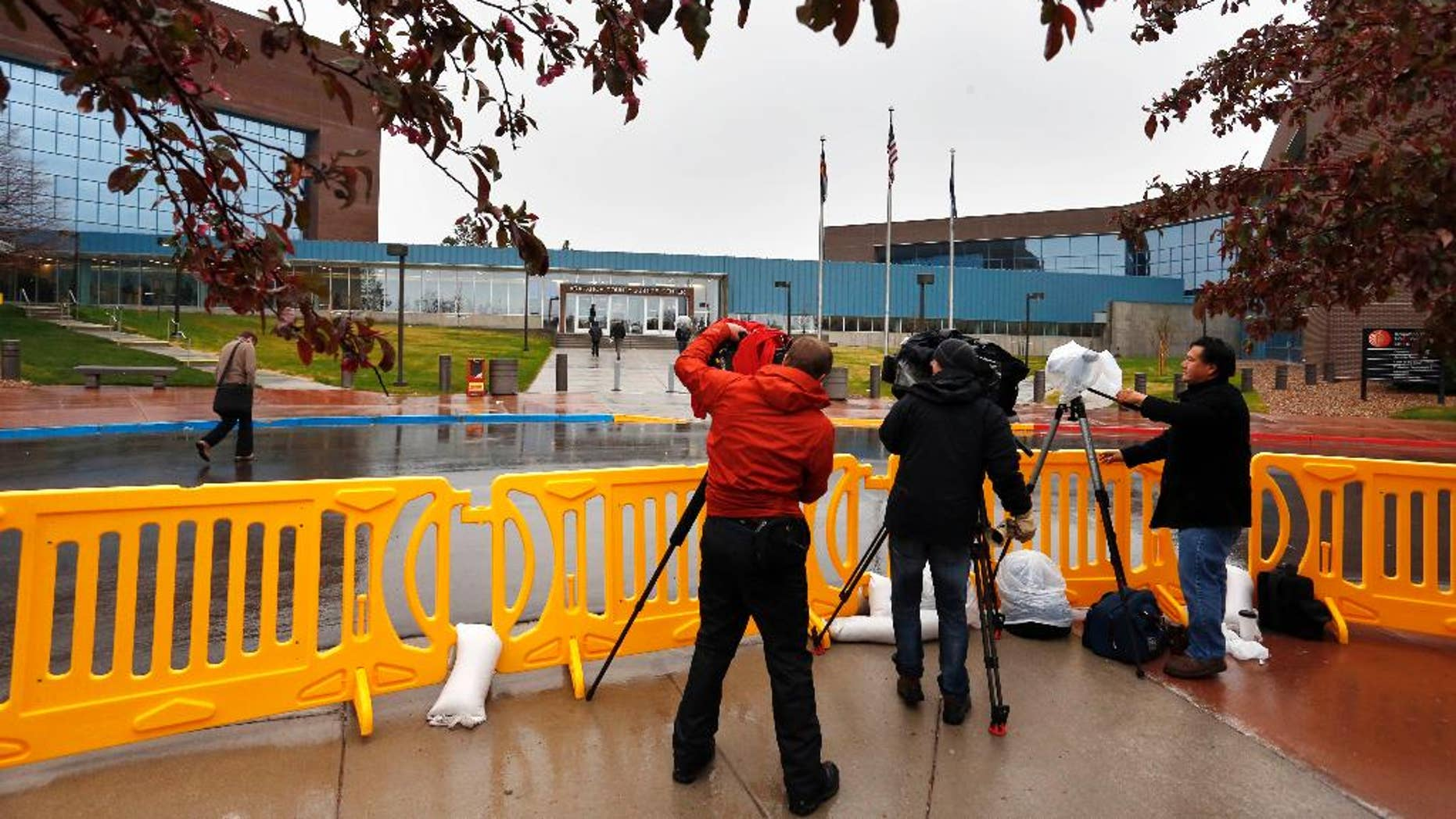 Television journalists film from within a media corral in front of the Arapahoe County Justice Center, on the first day of the trial of Aurora movie theater shootings defendant James Holmes, in Centennial, Colo., Monday April 27, 2015. As the trial begins, the key won't be whether he caused the carnage, but whether Holmes was sane at the time of the killings. (AP Photo/Brennan Linsley)