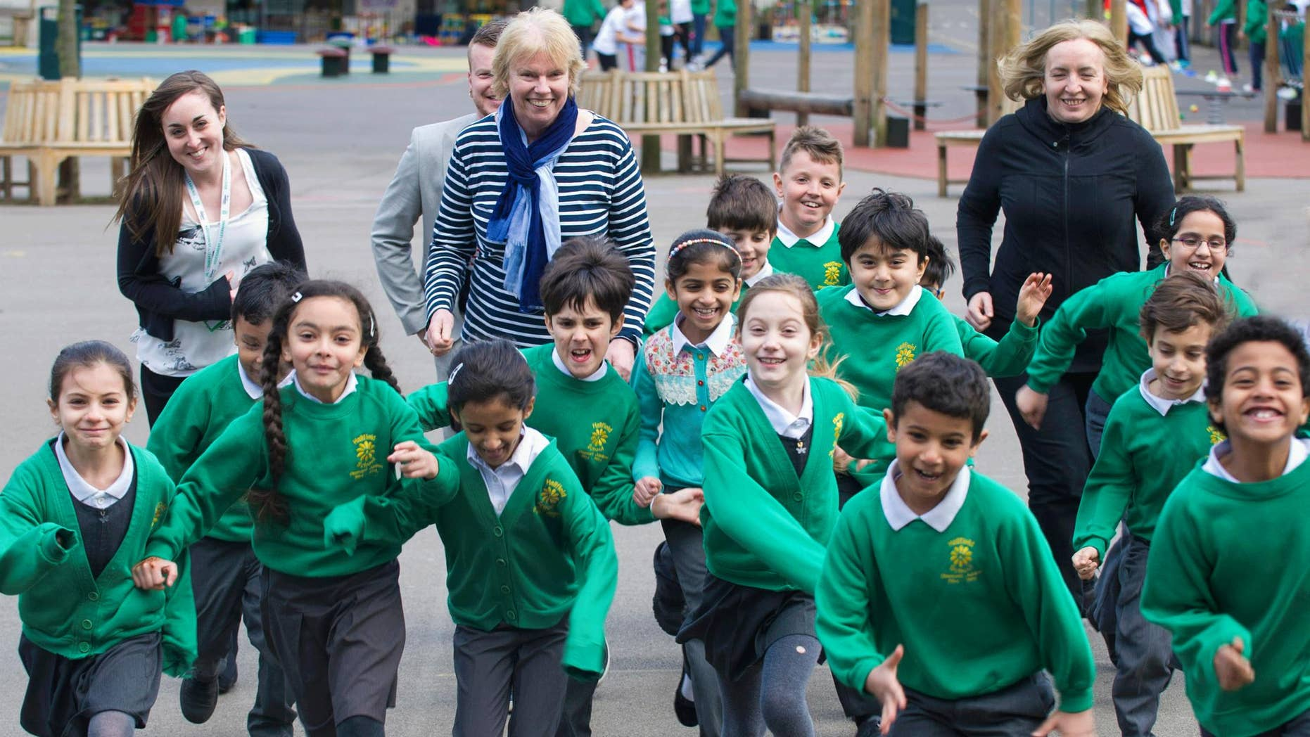 At the national launch of The Daily Mile in March 2016, founder Elaine Wyllie (center) runs with children at Hallfield Primary School in London.