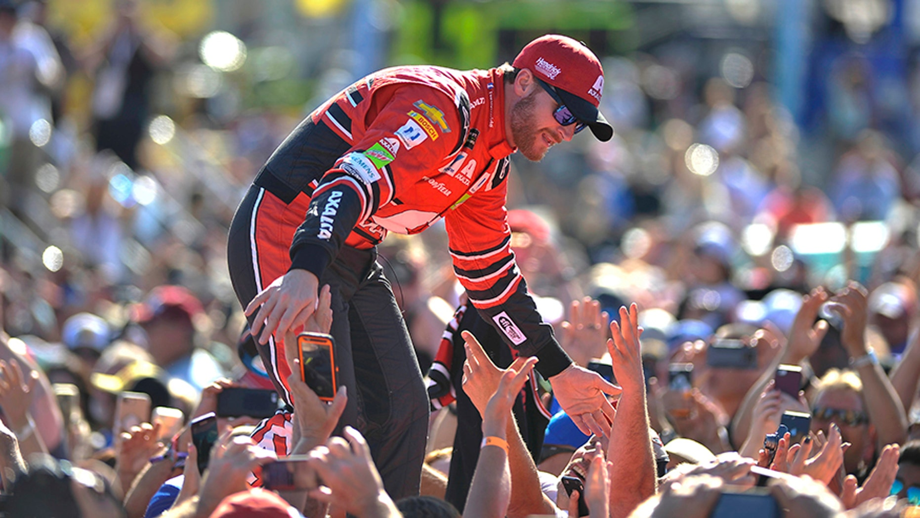 Dale Earnhardt Jr. greets fans as he is introduced before a NASCAR Cup Series auto race at Homestead-Miami Speedway in Homestead, Fla., Sunday, Nov. 19, 2017. (AP Photo/Gaston De Cardenas)