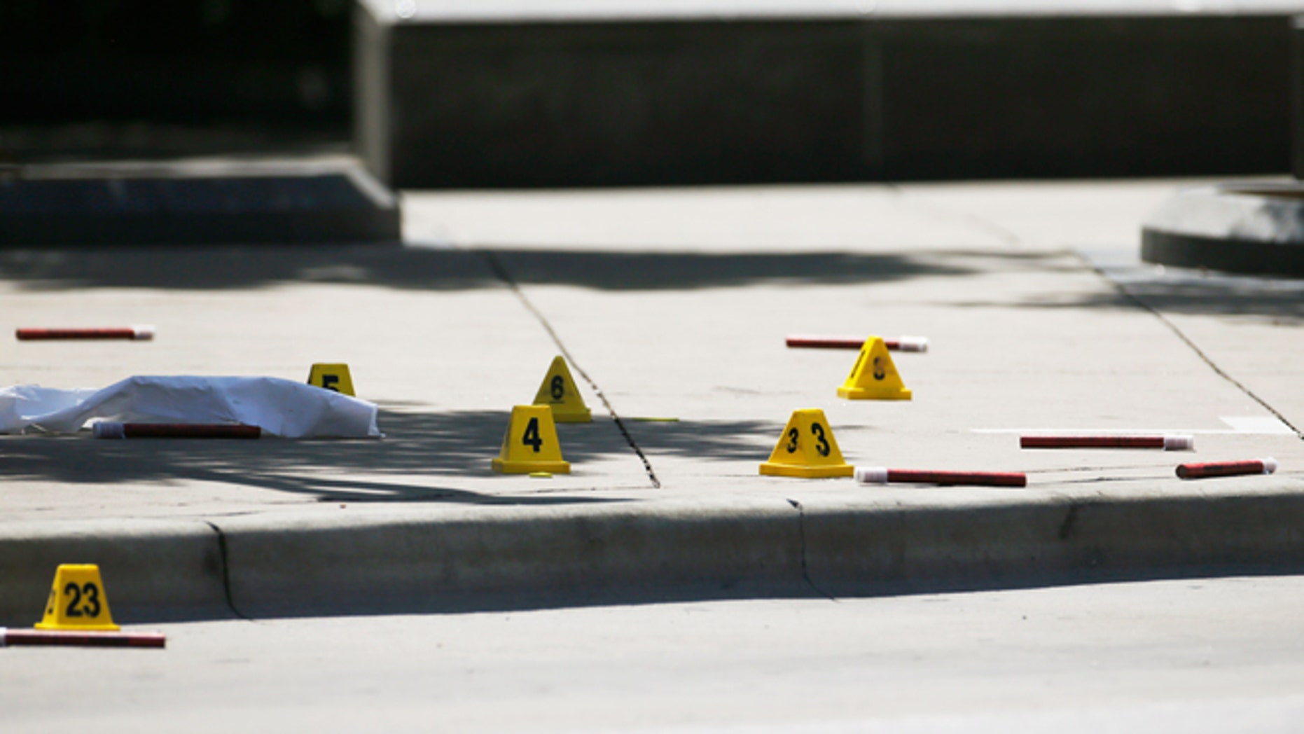 Markers litter the sidewalk as FBI investigators look over the crime scene in Dallas, Texas, U.S. July 8, 2016 following a Thursday night shooting incident that killed five police officers.  REUTERS/Carlo Allegri - RTX2KE0D