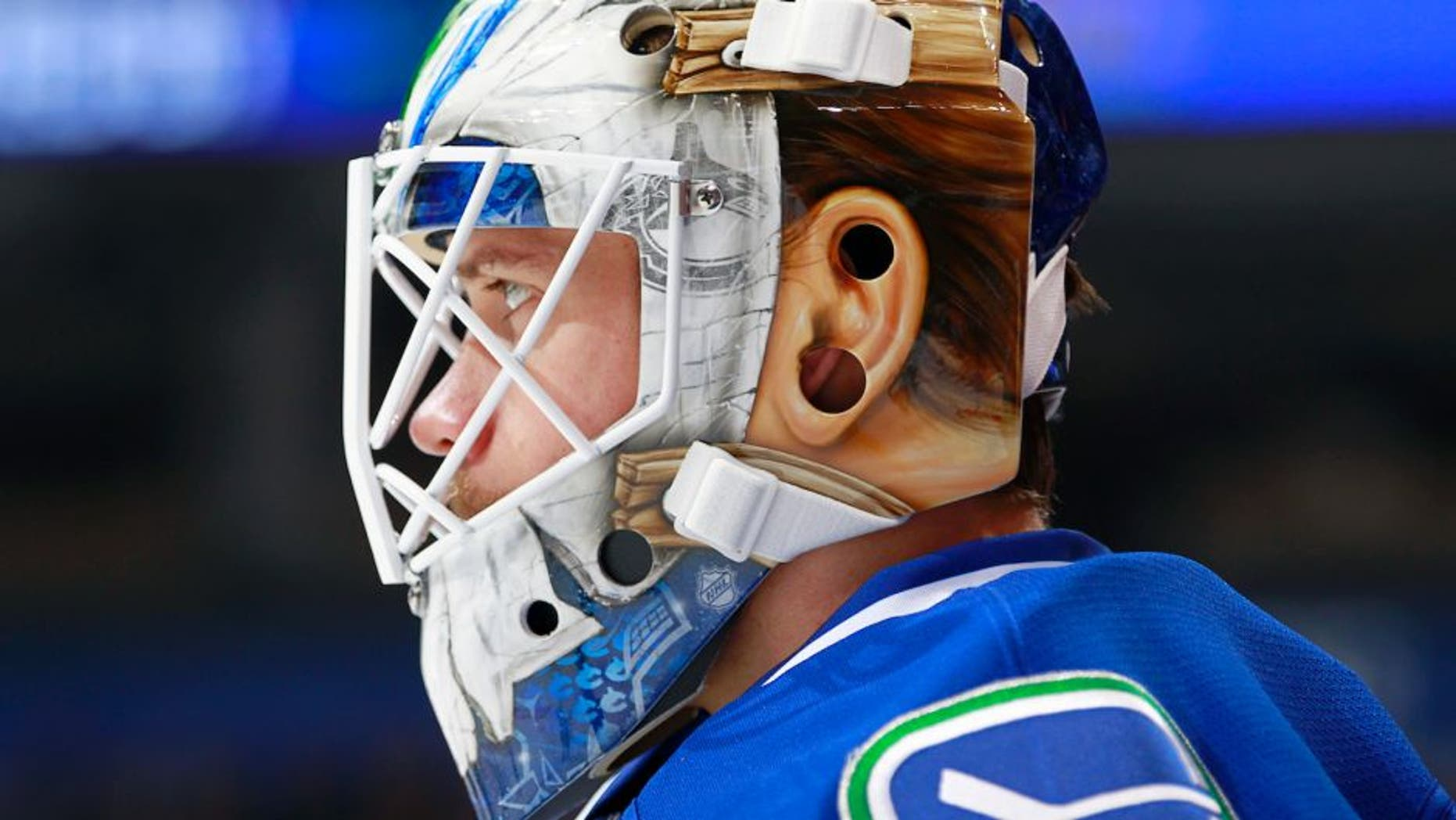 VANCOUVER, BC - NOVEMBER 13: Jacob Markstrom #25 of the Vancouver Canucks dons a new mask during warmup before their NHL game against the Dallas Stars at Rogers Arena November 13, 2016 in Vancouver, British Columbia, Canada. (Photo by Jeff Vinnick/NHLI via Getty Images)
