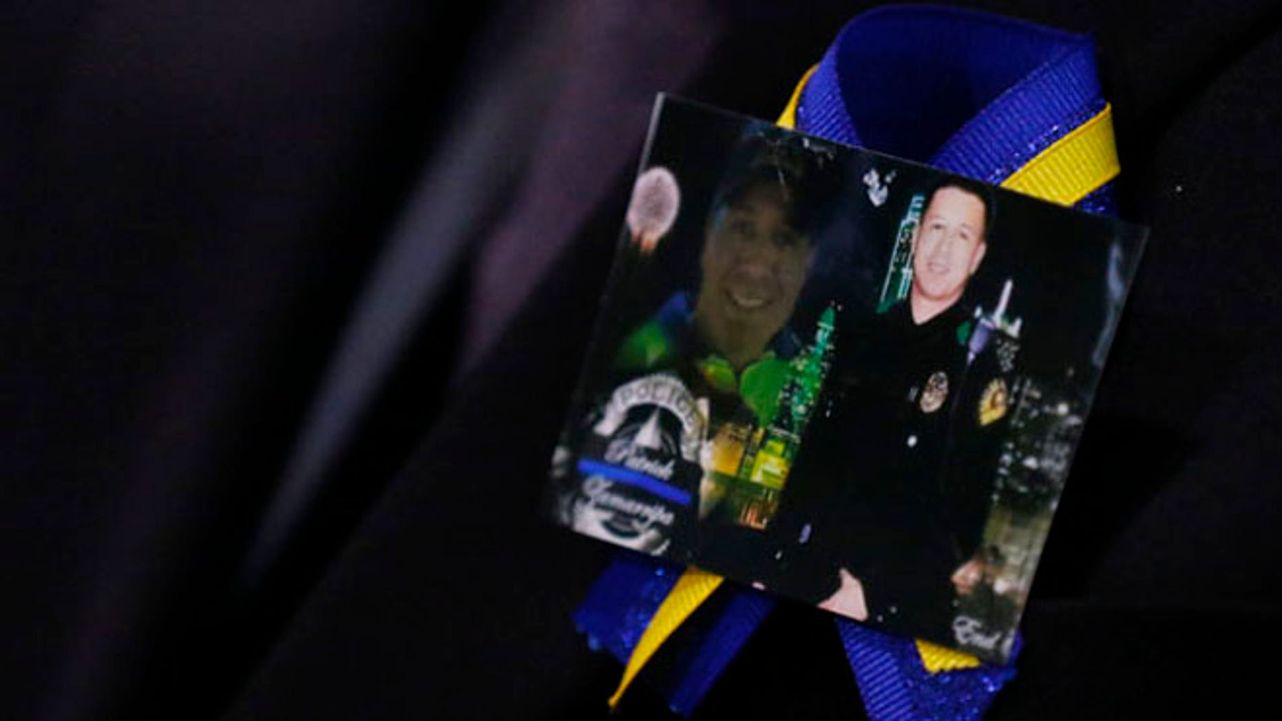 A family member wears a ribbon with photos of Patrick Zamarripa during a funeral service for Dallas police officer Patrick Zamarripa on Saturday, July 16, 2016 at Wilkerson-Greines Athletic Center in Fort Worth, Texas.  Zamarripa was one of the five officers killed July 7  by a lone gunman during a march to protest recent fatal shootings of black men in Minnesota and Louisiana by police. (Ashley Landis/The Dallas Morning News via AP, Pool)