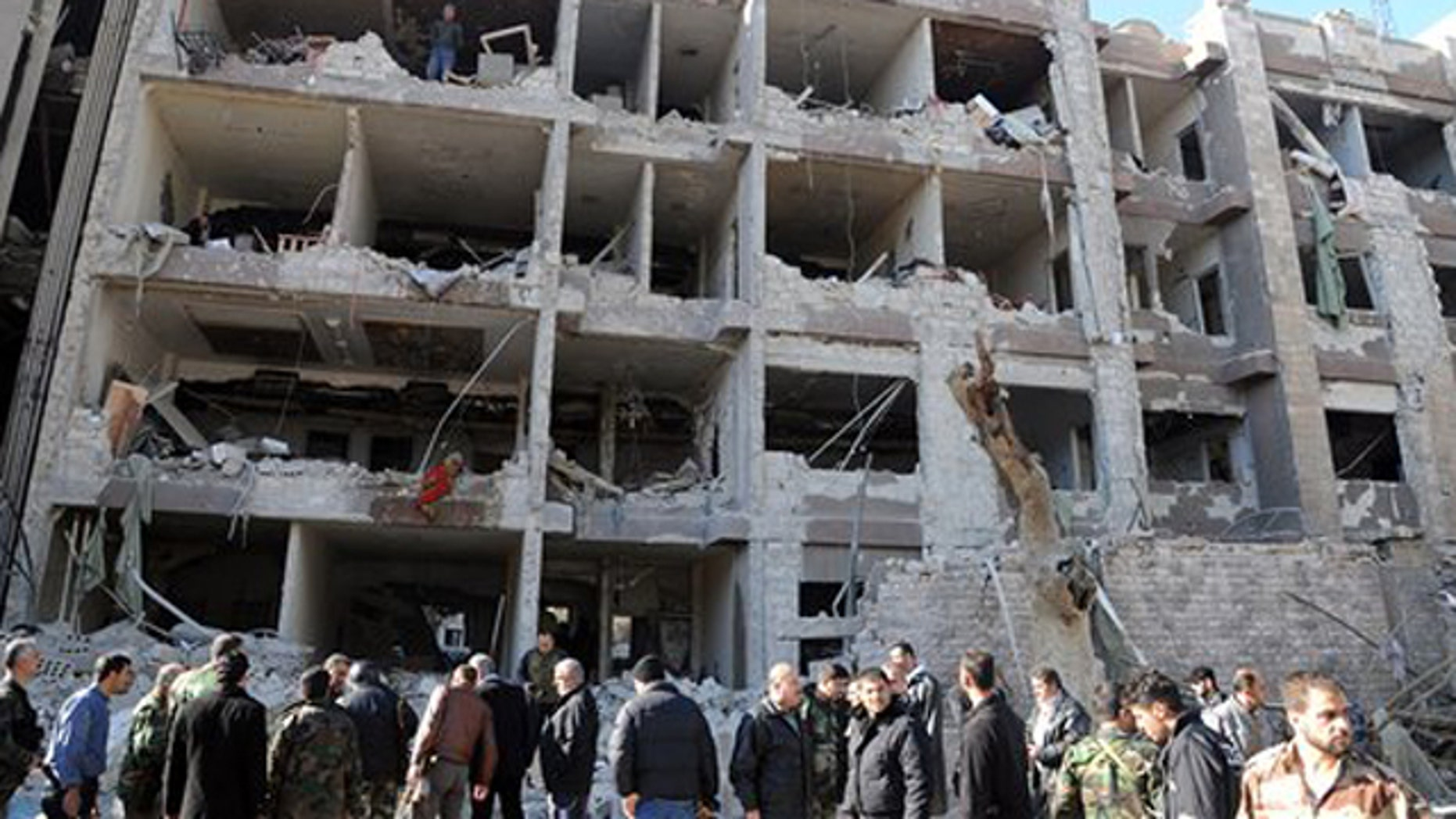 March 17, 2012: In this photo released by the Syrian official news agency SANA, Syrian security officers investigate a damaged building of the air intelligence forces, which was attacked by one of two explosions, in Damascus, Syria.