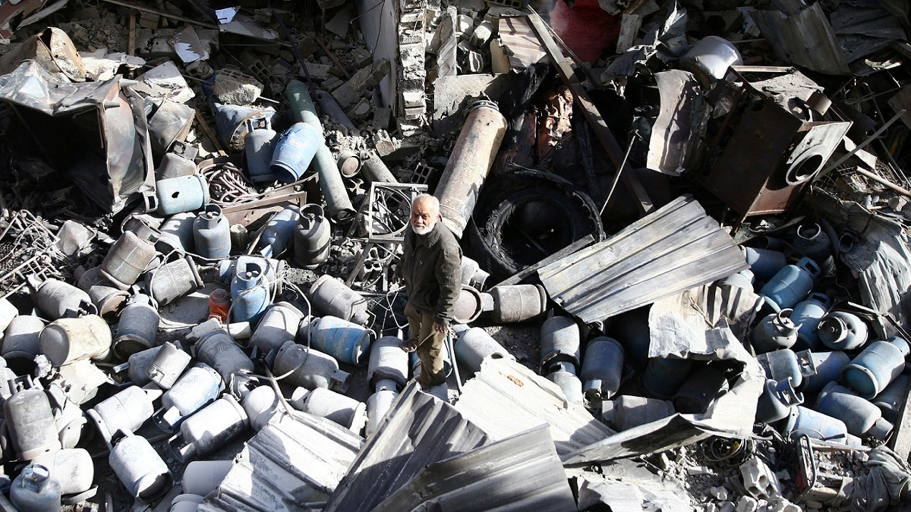 A man stands on the rubble of damaged buildings after an airstrike on the rebel-held town of Mesraba in the eastern Damascus suburb of Ghouta, Syria, November 26, 2017.