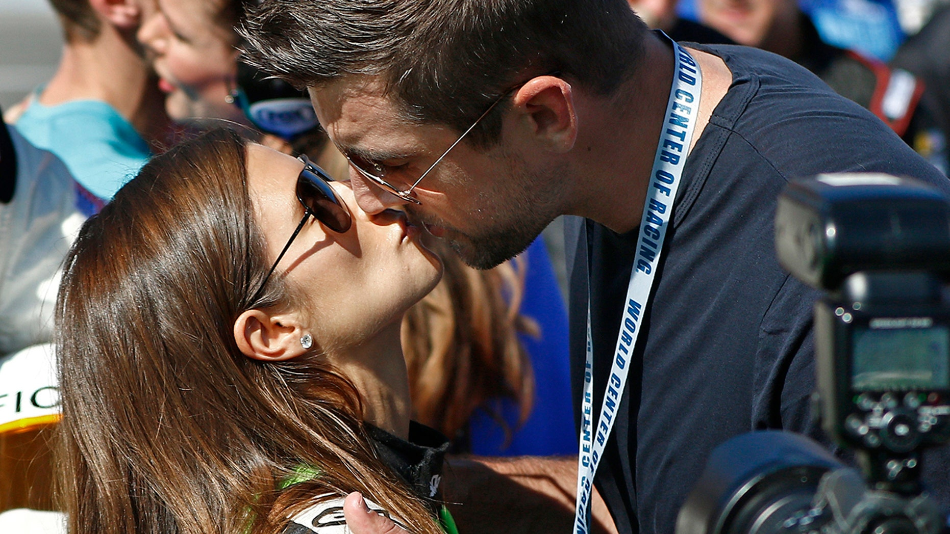 Danica Patrick, left, gets a kiss from Green Bay Packers quarterback Aaron Rodgers, right, before the NASCAR Daytona 500 Cup series auto race at Daytona International Speedway in Daytona Beach, Fla., Sunday, Feb. 18, 2018.