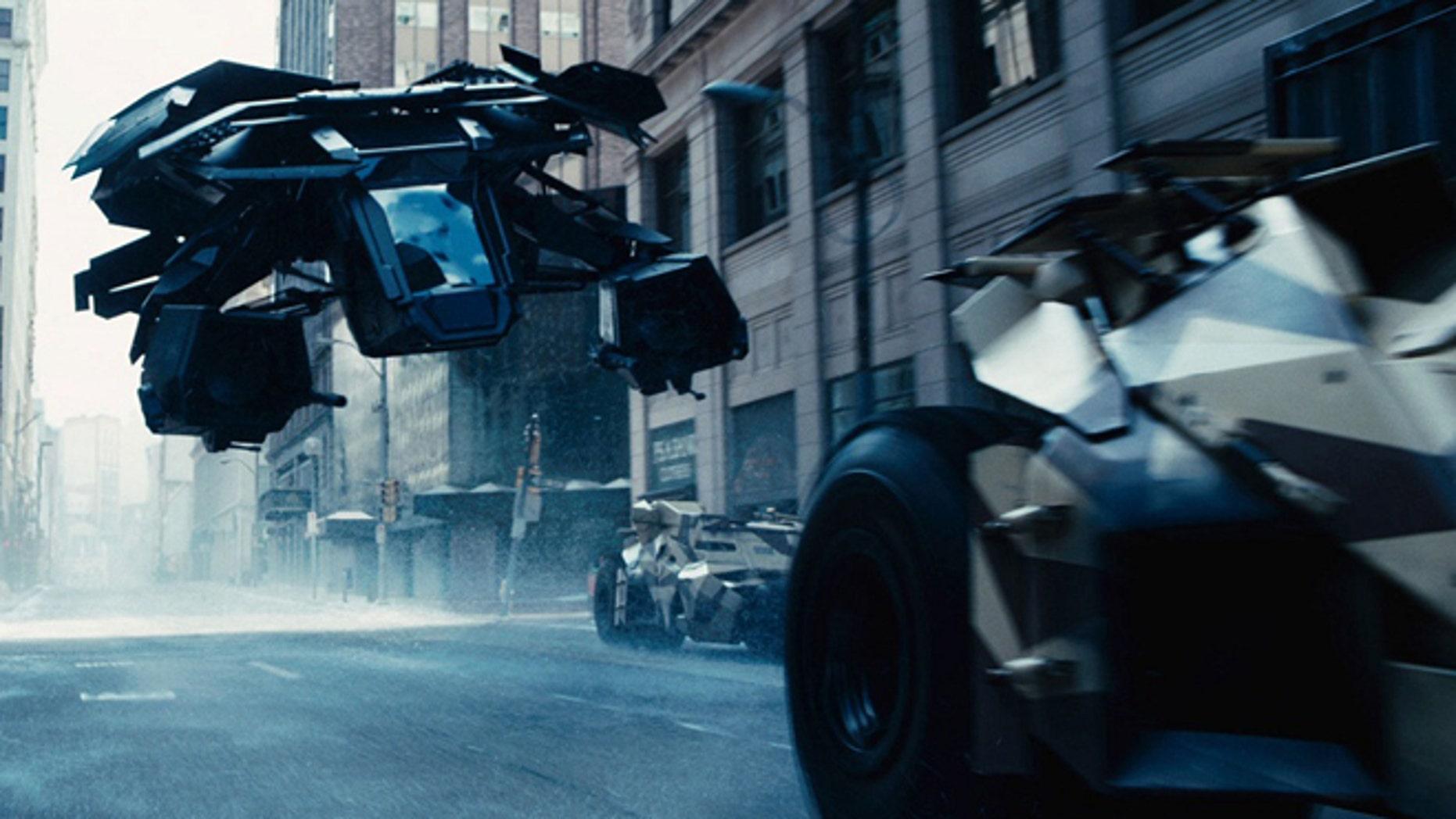 The Bat flying vehicle flies through Gotham's urban canyons in the Dark Knight Rises.