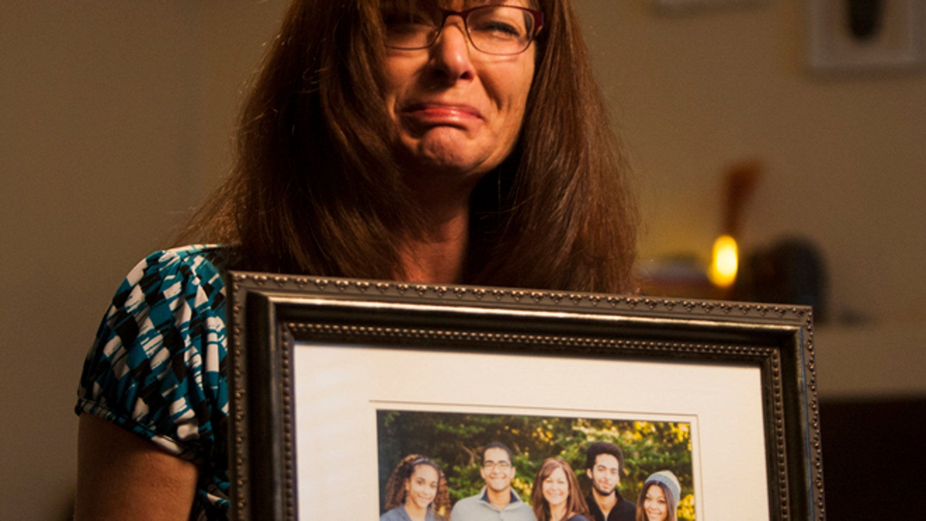 Sept. 12, 2014: Susan Hunt holds a photo of her family, including her son, Darrien Hunt, at her home in Saratoga Springs, Utah.