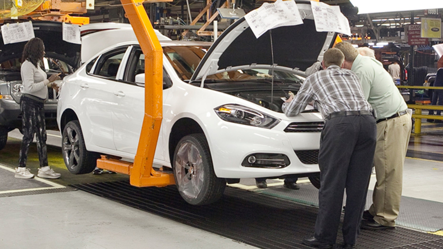 Workers manufacture a pre-production 2013 Dodge Dart.