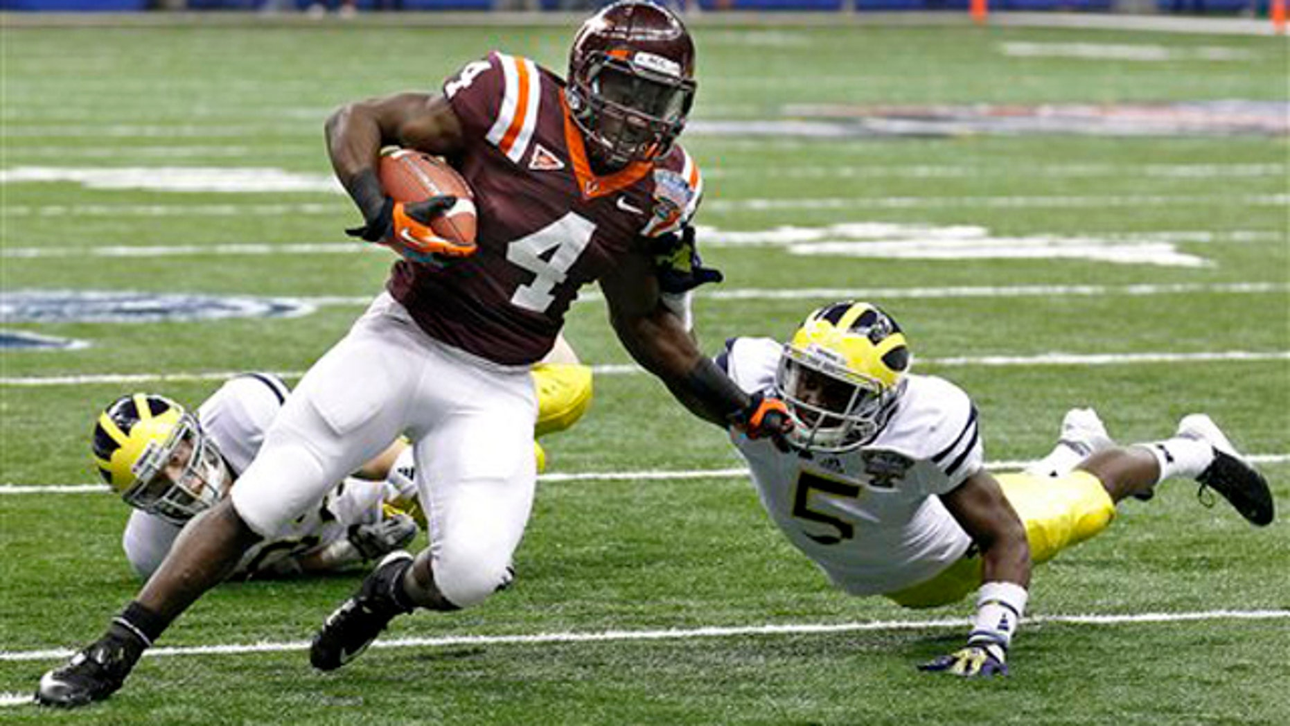 Jan. 3, 2012: Virginia Tech running back David Wilson (4) tries to turn the corner past Michigan cornerback Courtney Avery (5) and safety Jordan Kovacs during the first quarter of the Sugar Bowl NCAA college football game in New Orleans.