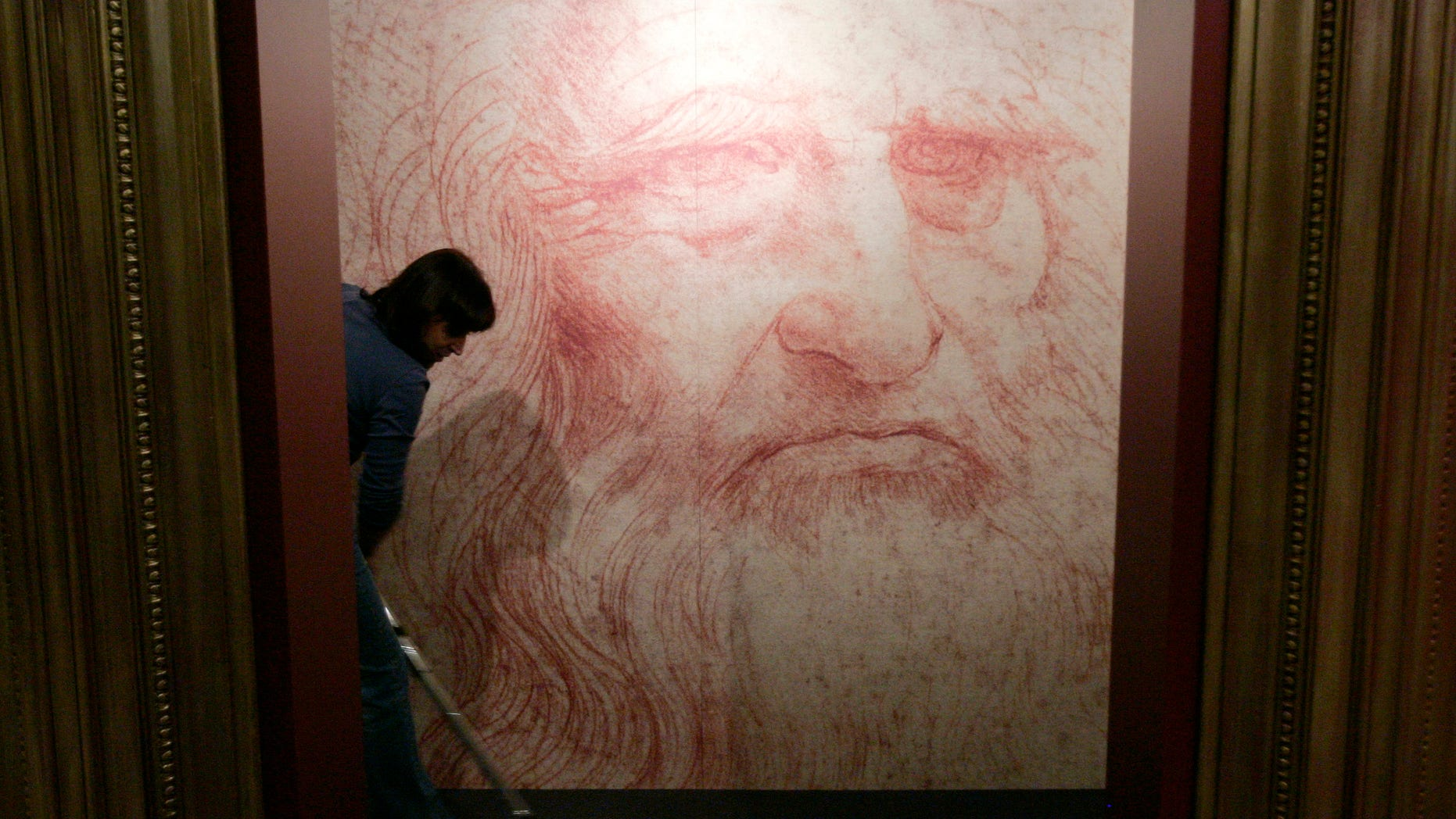 """A cleaner vacuums in front of a Leonardo da Vinci self-portrait drawn around 1515 or 1516, during the inauguration of the exhibition """"Leonardo da Vinci, the European Genius"""" in Brussels, August 17, 2007. (REUTERS/Francois Lenoir)"""
