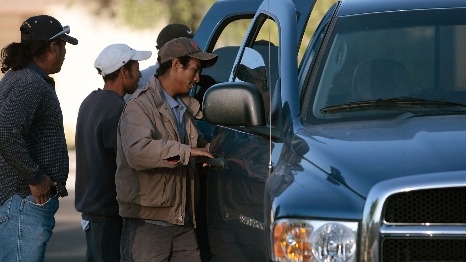 TUCSON, AZ - APRIL 05:  Hispanic day laborers open the doors to a truck as a man hires them to work manual labor April 5, 2008 in Tucson, Arizona.  Manual laborers, mostly undocumented workers from Mexico, frequent this corner in Tucson every morning before dawn, in an informal arrangement with local employers, who can pick up as many as they need for day-long jobs.  Much of the work up to now has been housing-related; but with the housing downturn, that work has largely dried up, and these laborers now often don't work more than once a week.  (Photo by Chris Hondros/Getty Images)