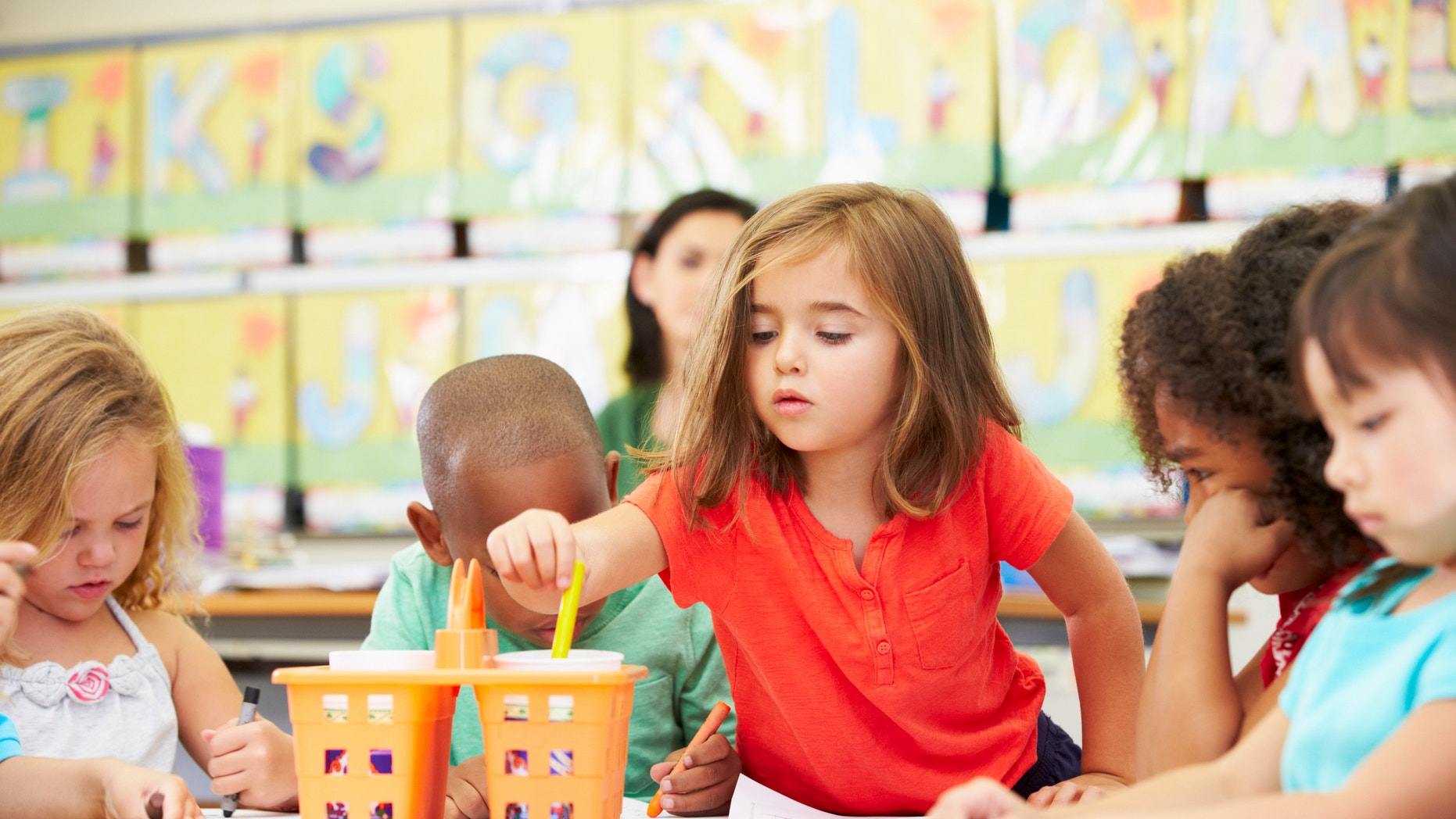 Group Of Elementary Age Children In Art Class With Teacher Reaching For Crayon