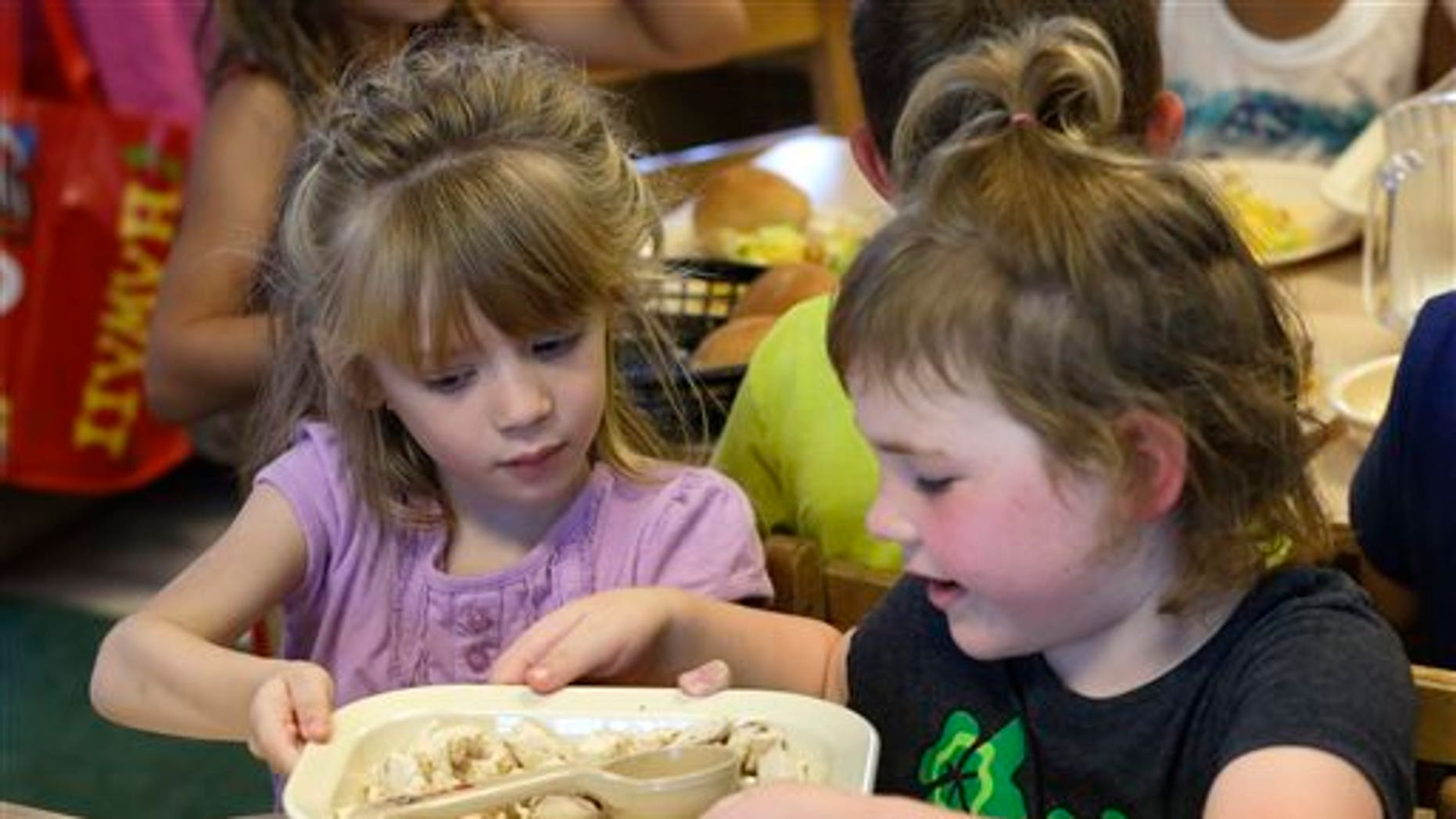 FILE -- June 24, 2015: Rebekah Webb, left, shares a family-style meal with Zoe Turner during lunch with other five-year-olds at the Olathe Family YMCA in Olathe, Kan. (AP Photo/Orlin Wagner)