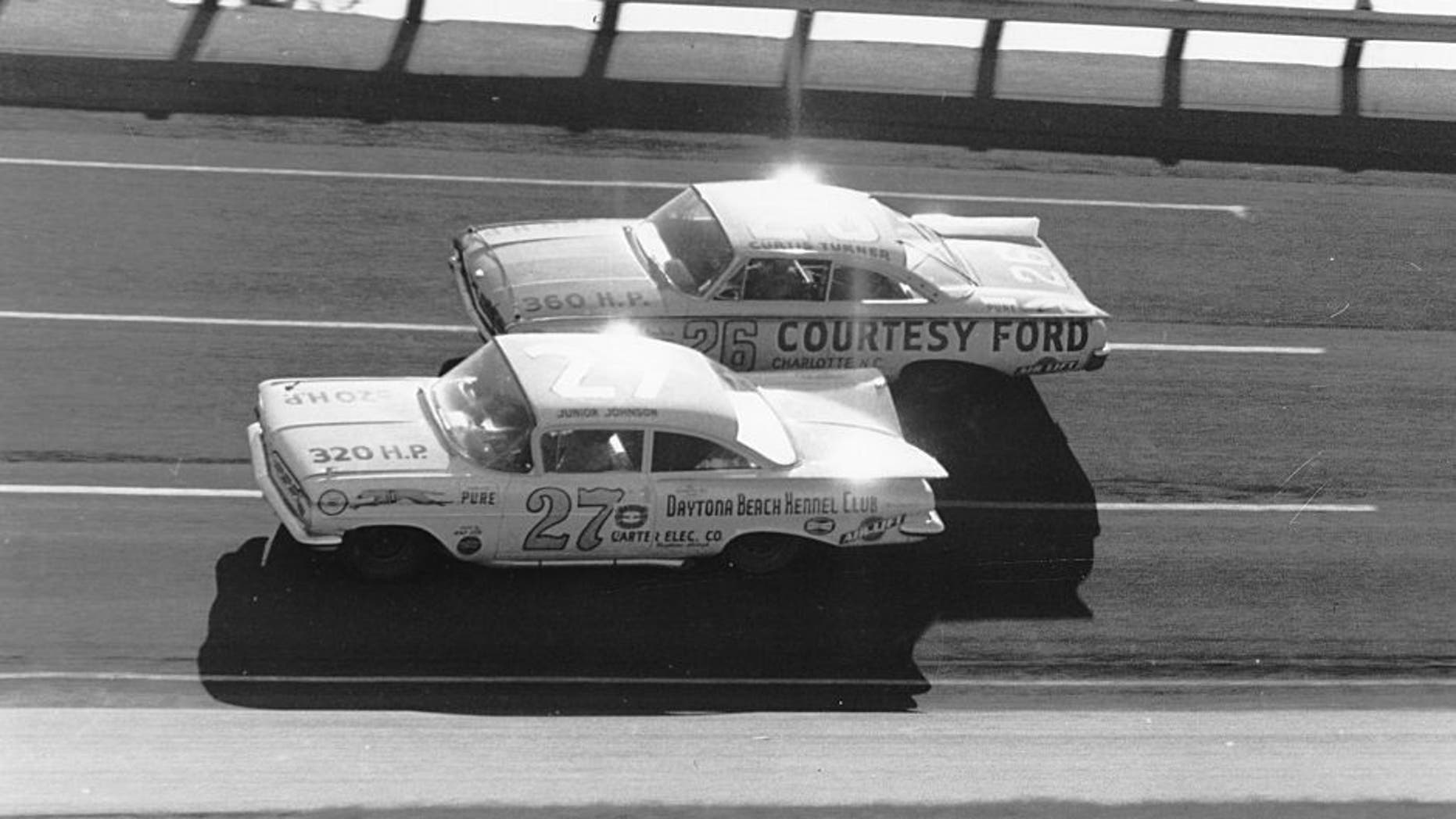 DAYTONA BEACH, FL - FEBRUARY 14: Eventual winner of the 1960 Daytona 500, Junior Johnson #27 ducks beneath Curtis Turner #26 who finished 7th during the Daytona 500 on February 14, 1960 at the Daytona International Speedway in Daytona Beach, Florida. There were so many wrecked and disabled cars following this event that NASCAR canceled the next two scheduled meets for fear of lack of participants. (Photo by ISC Archives via Getty Images)