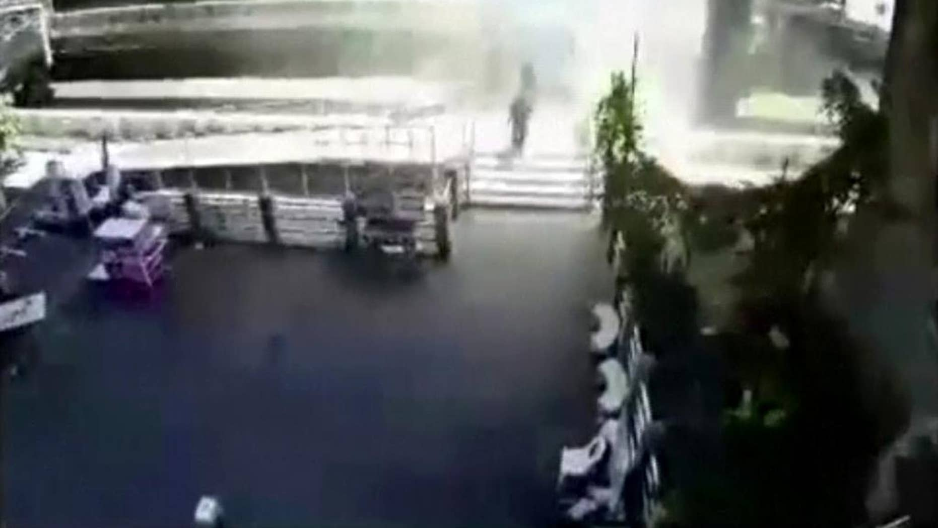FILE - In this Tuesday, Aug. 18, 2015, photo, people run from an explosion at a ferry pier in Bangkok, Thailand. No one was hurt in Tuesday's blast, but police say the explosive device was thrown from a bridge and blew up after falling into the river below. A Thai court on Thursday, Aug. 27, 2015,  issued an arrest warrant for an unnamed suspect in the riverside blast. (Photo via AP)