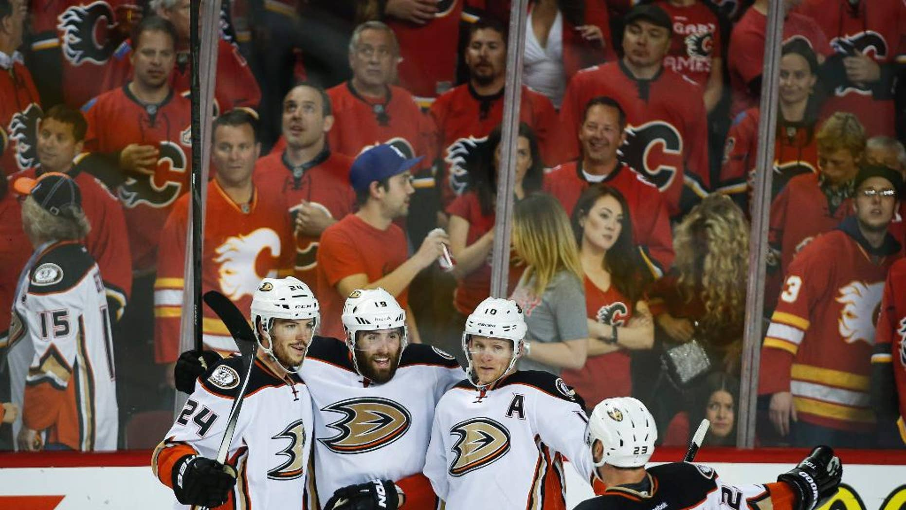 Anaheim Ducks' Simon Despres, from left, Patrick Maroon, Corey Perry and Francois Beauchemin celebrate their 4-2 win during the third period of Game 4 in an NHL hockey second-round playoff series against the Calgary Flames, Friday, May 8, 2015, in Calgary, Alberta. (Jeff McIntosh/The Canadian Press via AP) MANDATORY CREDIT