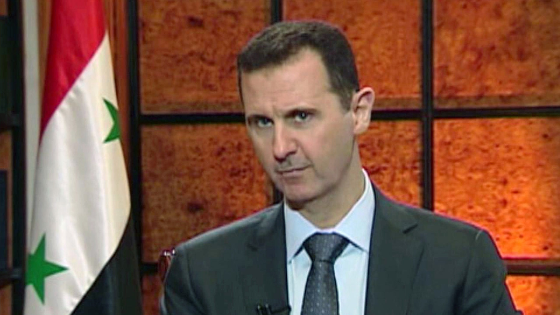 FILE - In this file image from video broadcast on Syrian state television Wednesday, April 17, 2013, President Bashar Assad speaks during an interview. The Syrian government wants more details before deciding whether to take part in a proposed U.S.-Russian initiative to negotiate a peaceful end to Syria's crisis, the country's information minister said Tuesday, May 14, 2013, staking out a similar position to the main opposition group. One of the key sticking points in even bringing the sides to the table for talks has been the role of Assad in any negotiated transition.(AP Photo/Syrian State TV via AP video, File)