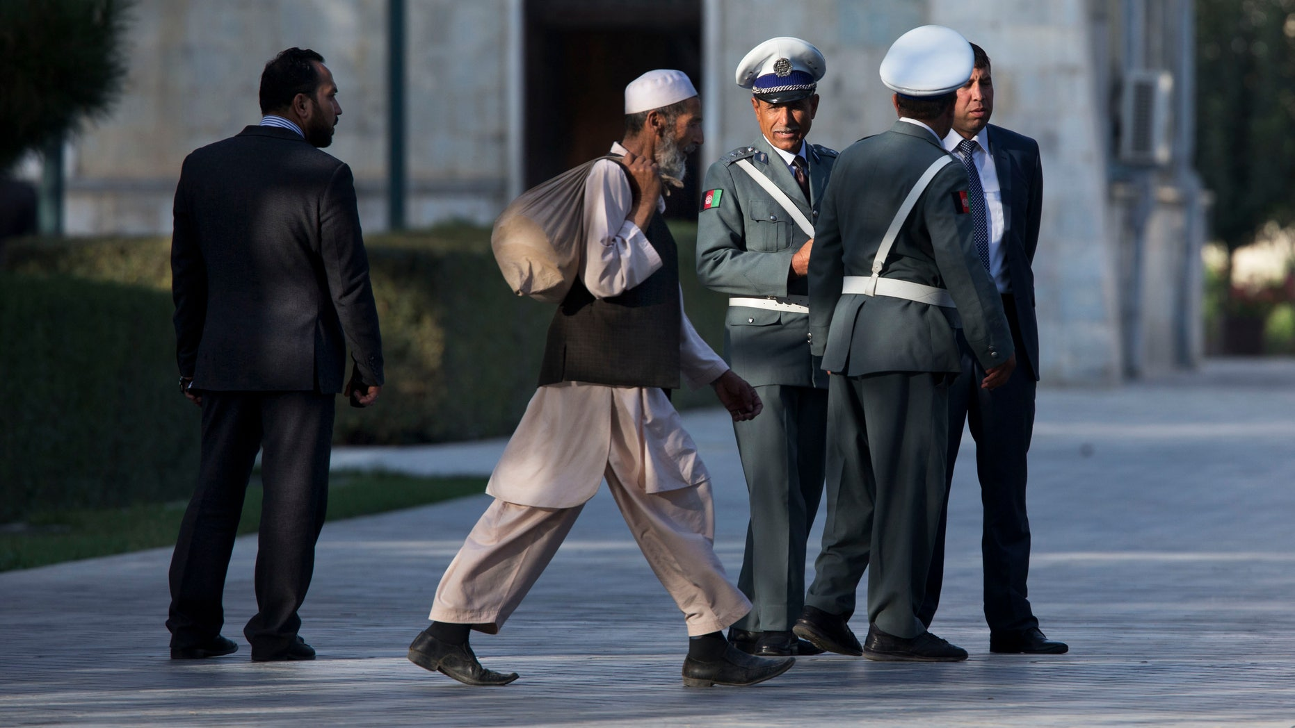 A worker walks past Afghan guards as they wait for a news conference that has been delayed between U.S. Secretary of State John Kerry and Afghan President Hamid Karzai at the presidential palace on the second day of an unannounced stop in Kabul, Afghanistan, on Saturday, Oct. 12, 2013. Kerry extended talks Saturday with Karzai on a bilateral security agreement with the United States, and while work remains to be done a deal could be struck by the end of the day, a presidential spokesman said.  (AP Photo/Jacquelyn Martin, Pool)