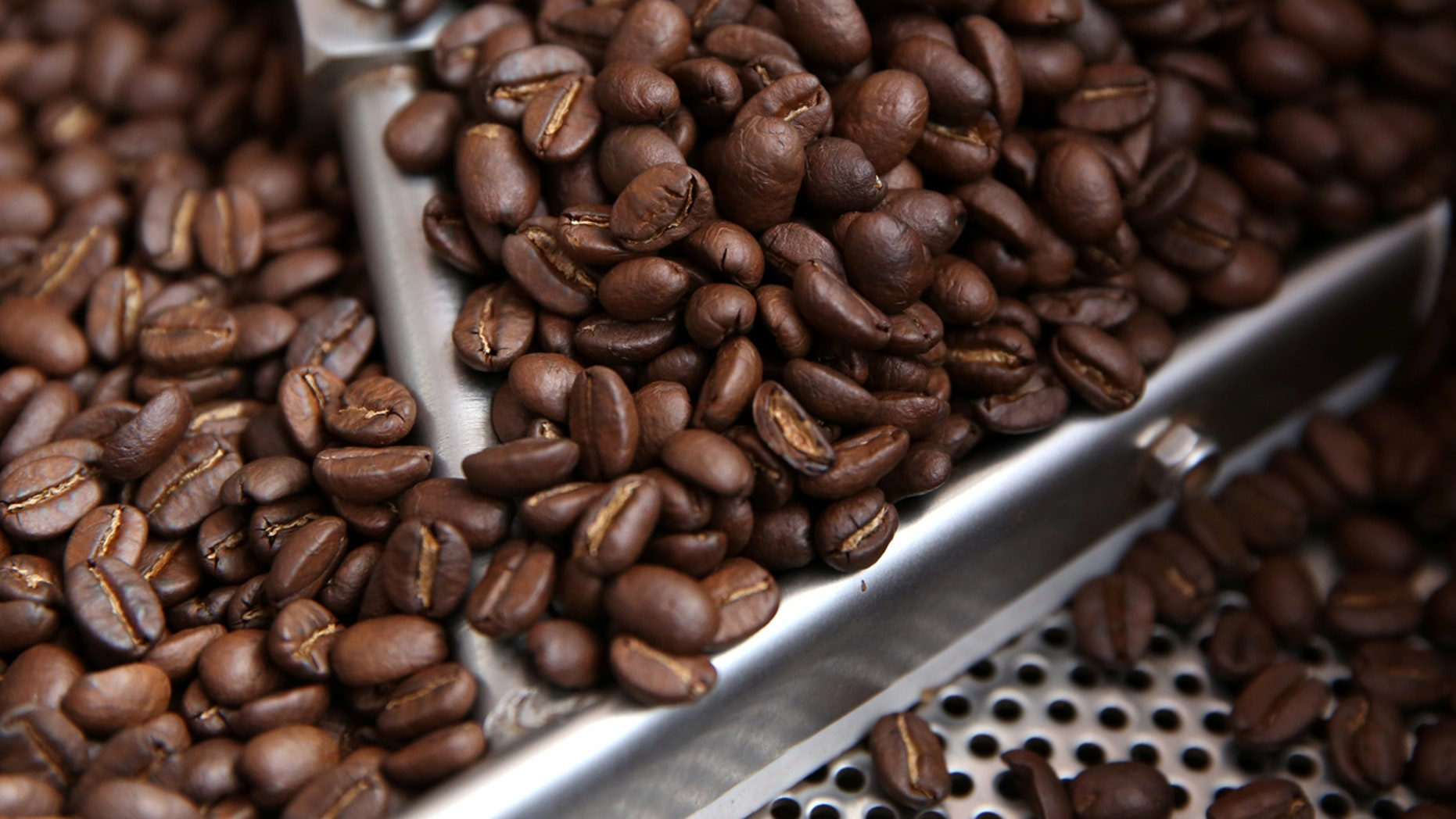 FILE: Coffee beans are seen in a roaster.