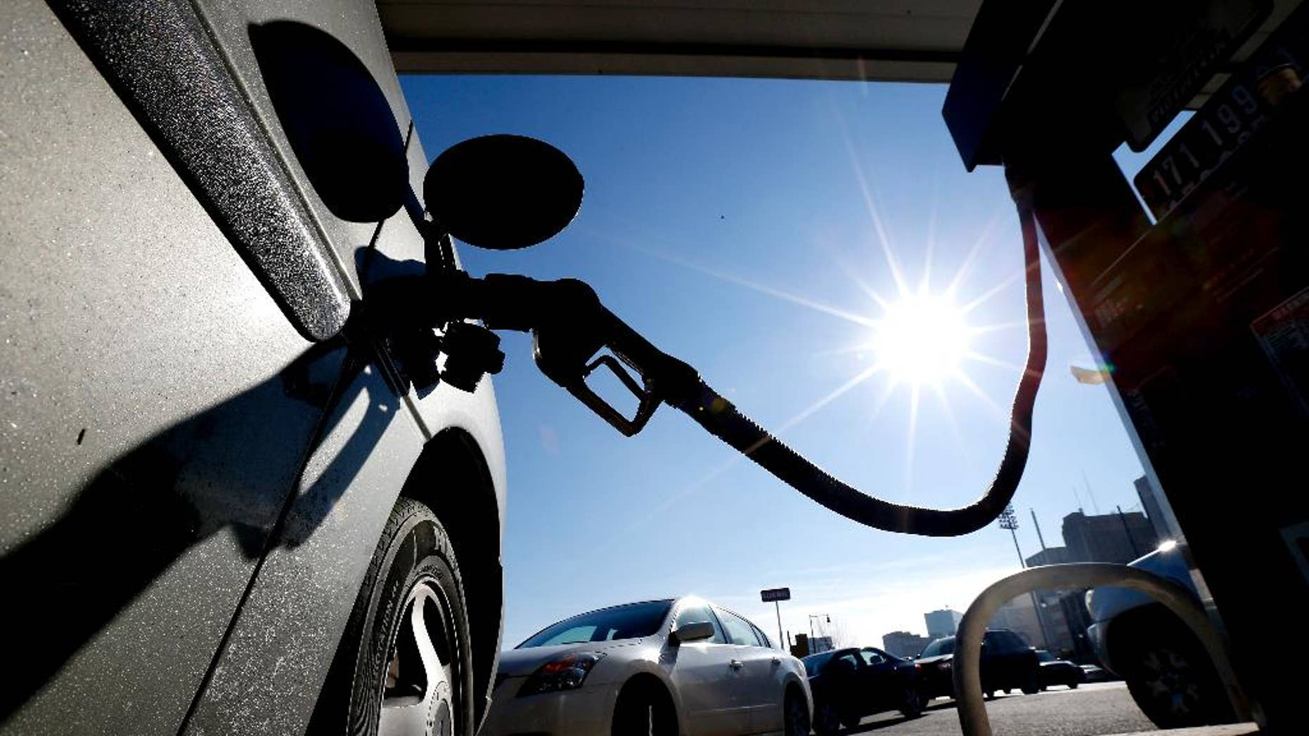 FILE - In this Friday, Jan. 23, 2015, file photo, vehicles form a line behind a motorist gassing up at a gas station in Newark, N.J. The Commerce Department releases its February report on consumer spending, which accounts for 70 percent of economic activity, on Monday, March 30, 2015. (AP Photo/Julio Cortez, File)