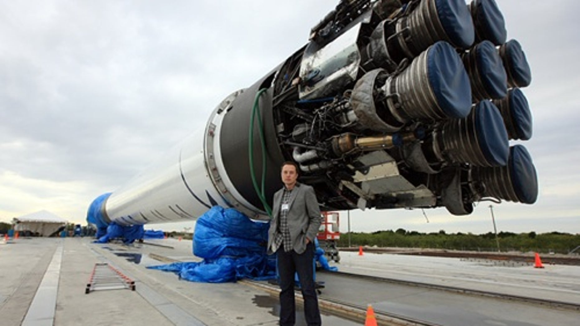 SpaceX Founder, Elon Musk, stands in front of his newest toy -- the Falcon 9 rocket.