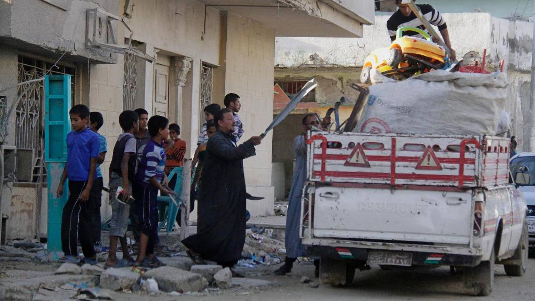 People collect their belongings from their residence as the Egyptian army demolish homes on the Egyptian side of border town of Rafah, northeast of Cairo, Egypt, Thursday, Nov. 6, 2014. In the deadliest-ever militant attack on the military, at least 30 soldiers were killed late last month in Sinai, prompting el-Sissi to declare a state of emergency in northern Sinai and order the eviction of some 10,000 people from the town of Rafah on the border with the Gaza Strip. (AP Photo/El Shorouk newspaper, Ahmed Abd El-Latif) EGYPT OUT