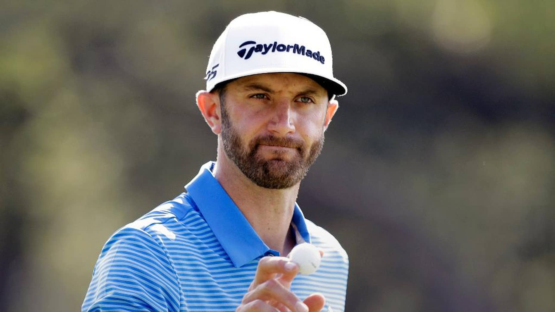 FILE - In this March 26, 2017, file photo, Dustin Johnson waves to the gallery after a birdie putt on the sixth hole during semifinal play at the Dell Technologies Match Play golf tournament at the Austin County Club in Austin, Texas. Johnson's injured back must be feeling better. The world's No. 1 player said he'll return to the PGA Tour at the Wells Fargo Championships at Eagle Point Golf Club from May 4-7. The Wells Fargo Championship announced Johnson's status Thursday, April 13, 2017. (AP Photo/Eric Gay, File)