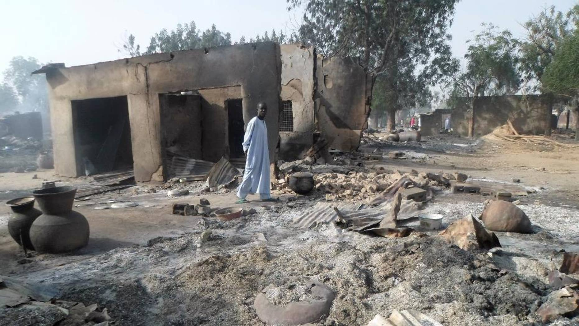 """FILE - In this Sunday Jan. 31, 2016 file photo, a man walks past burnt out houses following an attack by Boko Haram in Dalori village near Maiduguri, Nigeria. Abubakar Shekau says he still leads Boko Haram, exposing the biggest rift yet among Nigeria's Islamic insurgents and possibly paving the way for a break from the Islamic State group. The Islamic State on Wednesday, Aug. 3, 2016 announced that Abu Musab al-Barnawi is the new leader of its so-called West Africa province. But an audio speech Thursday purporting to be from Shekau criticizes al-Barnawi as """"an infidel."""" (AP Photo/Jossy Ola, File)"""