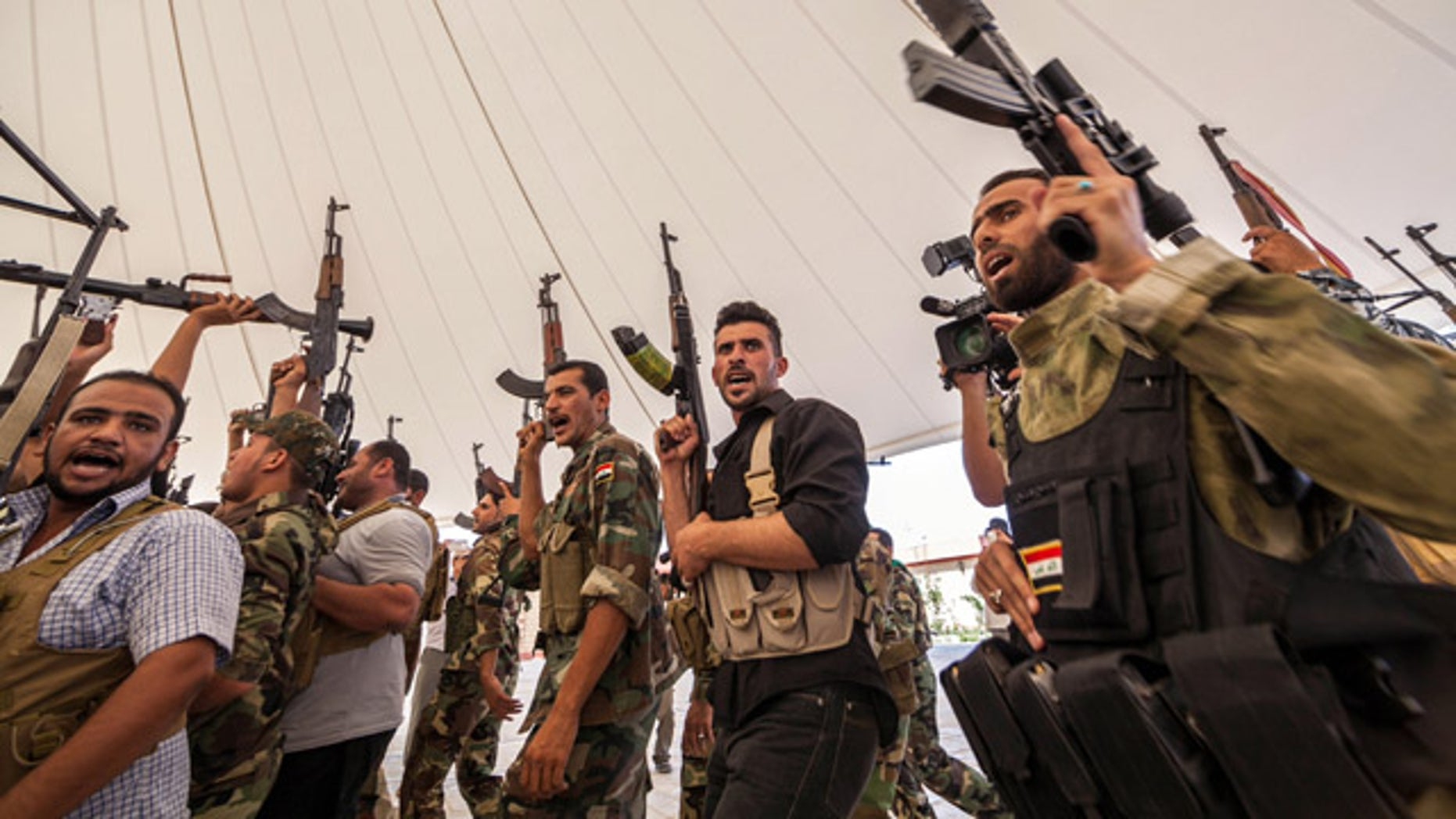 June 25, 2014: An Iraqi volunteer force chant slogans against the Al Qaeda-inspired Islamic State of Iraq and the Levant during training in the Shiite holy city of Karbala, 50 miles south of Baghdad. (AP Photo/Ahmed al-Husseini)