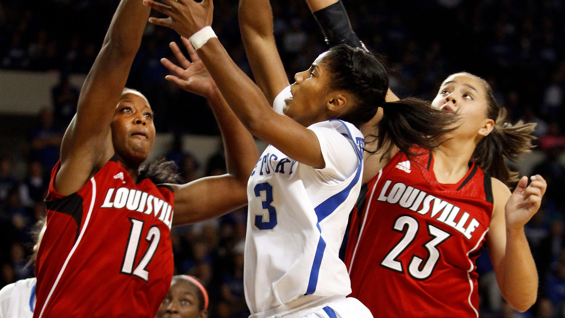 Kentucky's Janee Thompson (3) shoots between Louisville's Shawnta' Dyer (12) and Shoni Schimmel (23) during the first half of an NCAA college basketball game on Sunday, Dec. 1, 2013, in Lexington, Ky.  (AP Photo/James Crisp)
