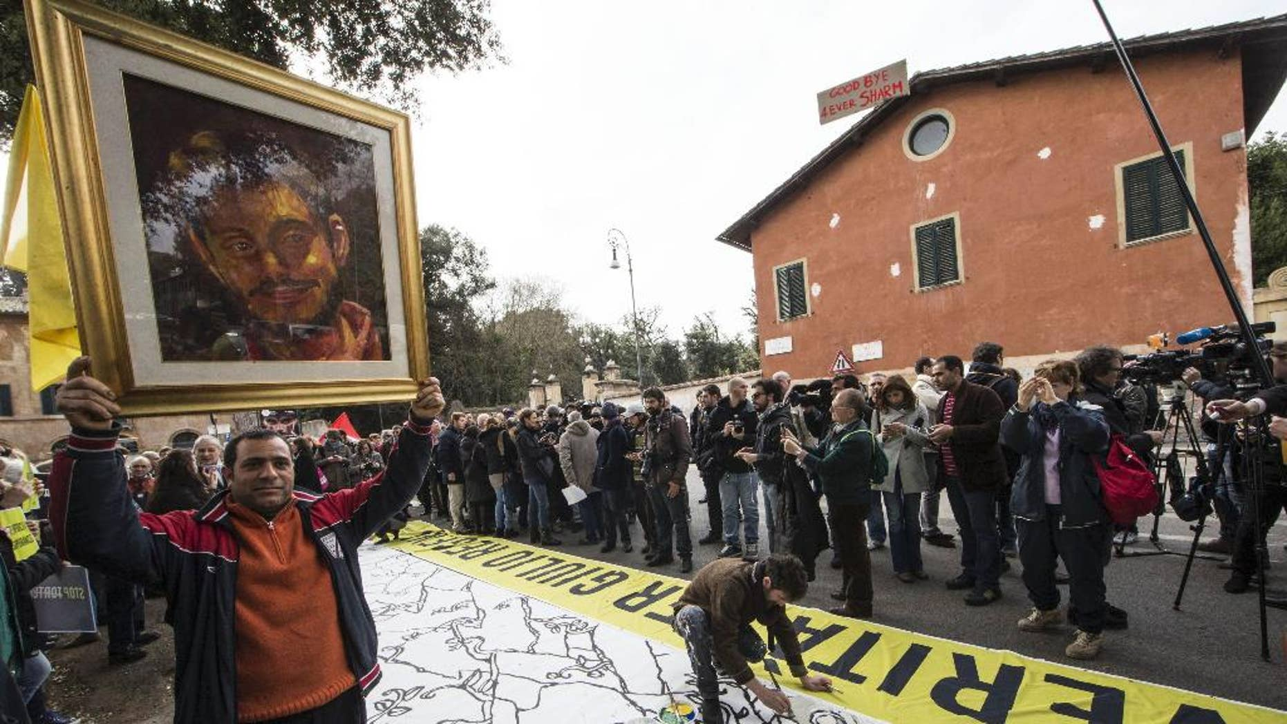 FILE - In this Feb. 25, 2016 file photo, a man holds up a portrait of Giulio Regeni, the Italian student slained in Cairo, as several dozen people stage a sit-in outside Egypt's embassy in Rome. Egypt's chief prosecutor has told Italian authorities Cairo police investigated an Italian researcher weeks before the young man was found tortured to death in the Egyptian capital, according to a statement Friday, Sept. 9, 2016 from both sides. (Massimo Percossi/ANSA via AP, File)