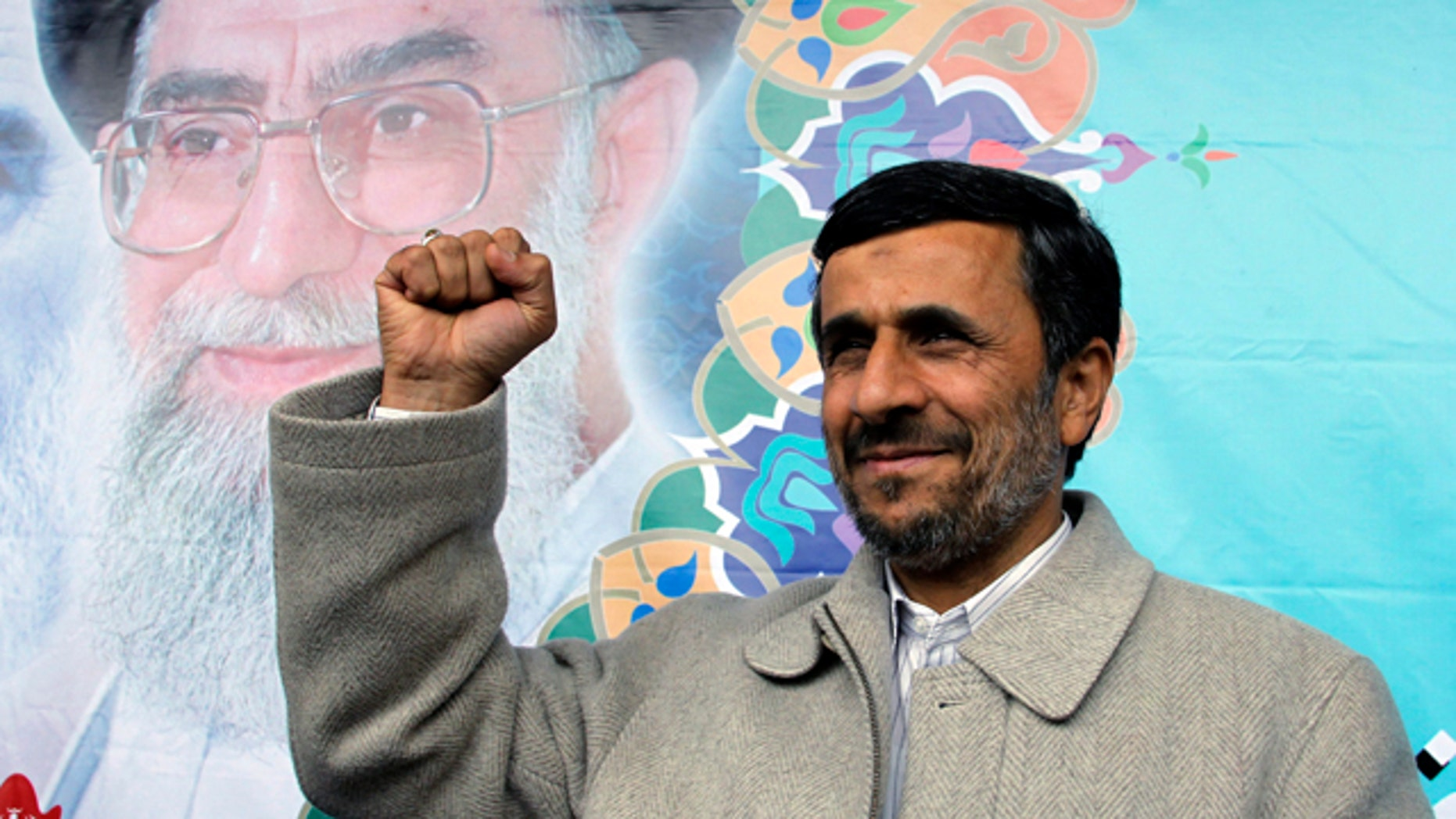 February 2011: Iranian President Mamoud Ahmadinejad, shown in this file photo pumping his fist, reportedly has been butting heads with Supreme Leader Ayatollah Ali Khamenei, in background.