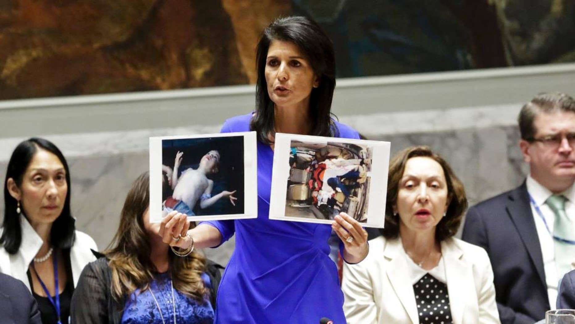 Nikki Haley, United States' Ambassador United Nations, shows pictures of Syrian victims of chemical attacks as she addresses a meeting of the Security Council on Syria at U.N. headquarters, Wednesday, April 5, 2017. (AP Photo/Bebeto Matthews)